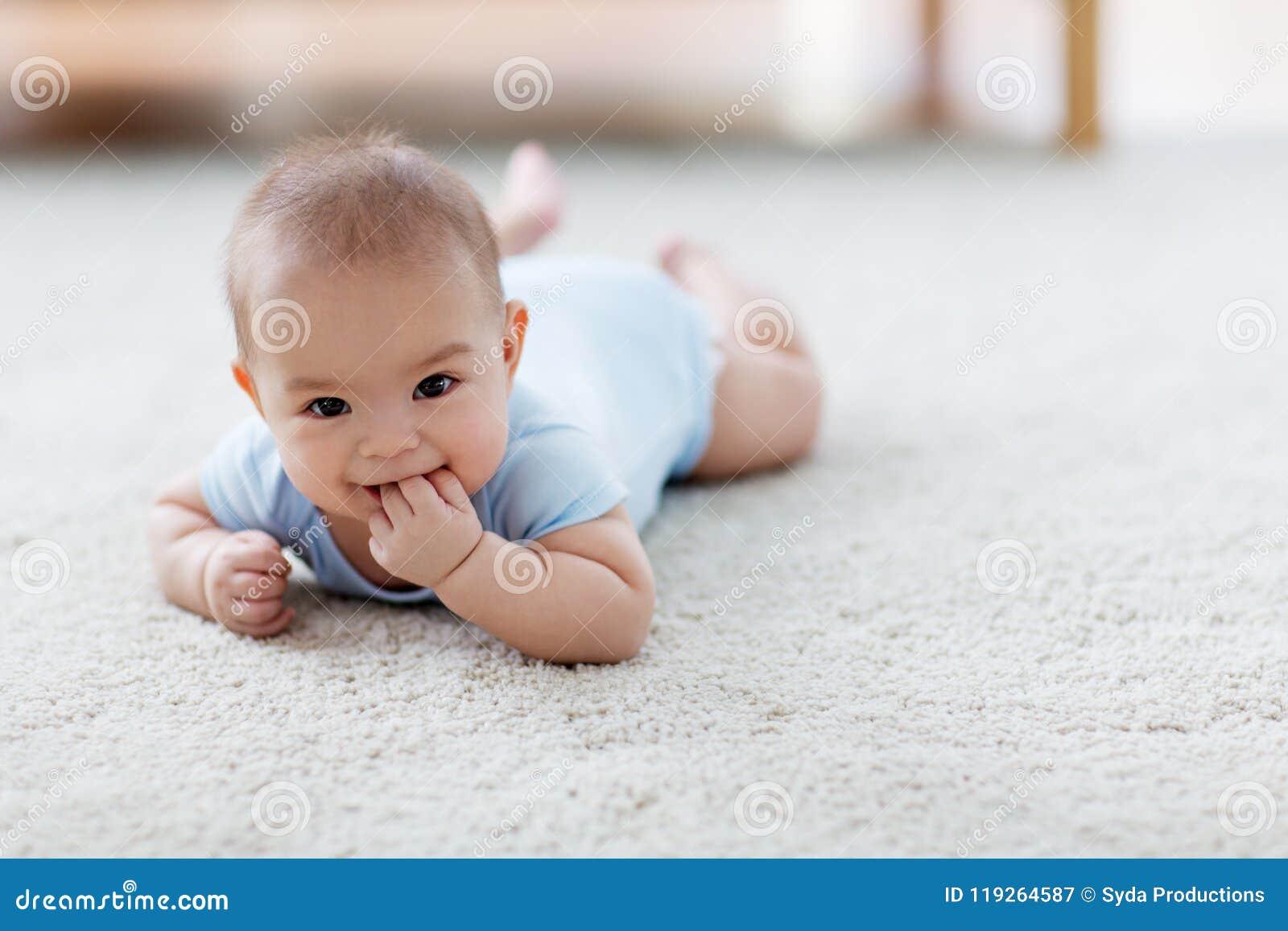 Sweet little asian baby boy lying on floor