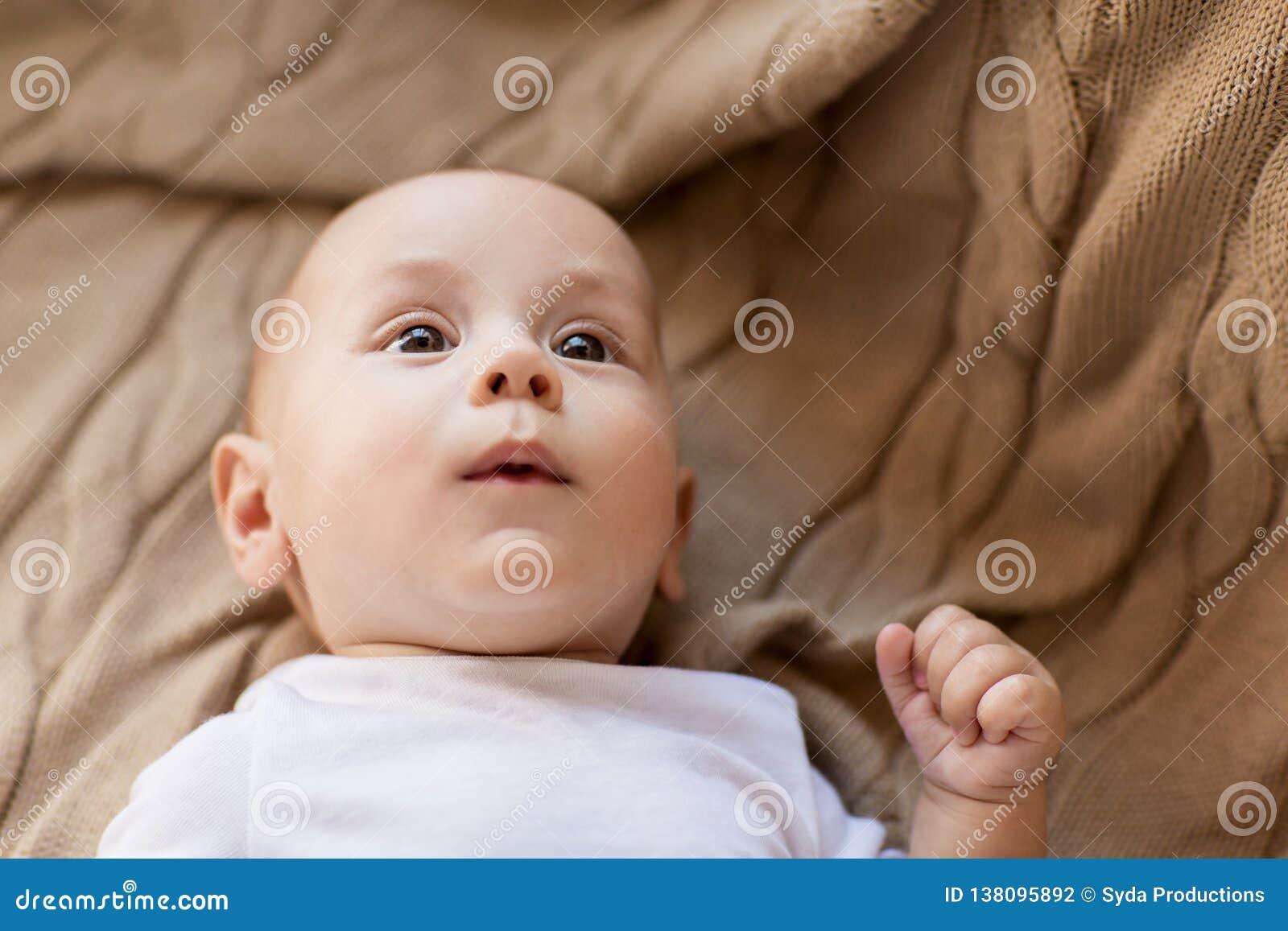 Sweet little baby boy lying on knitted blanket