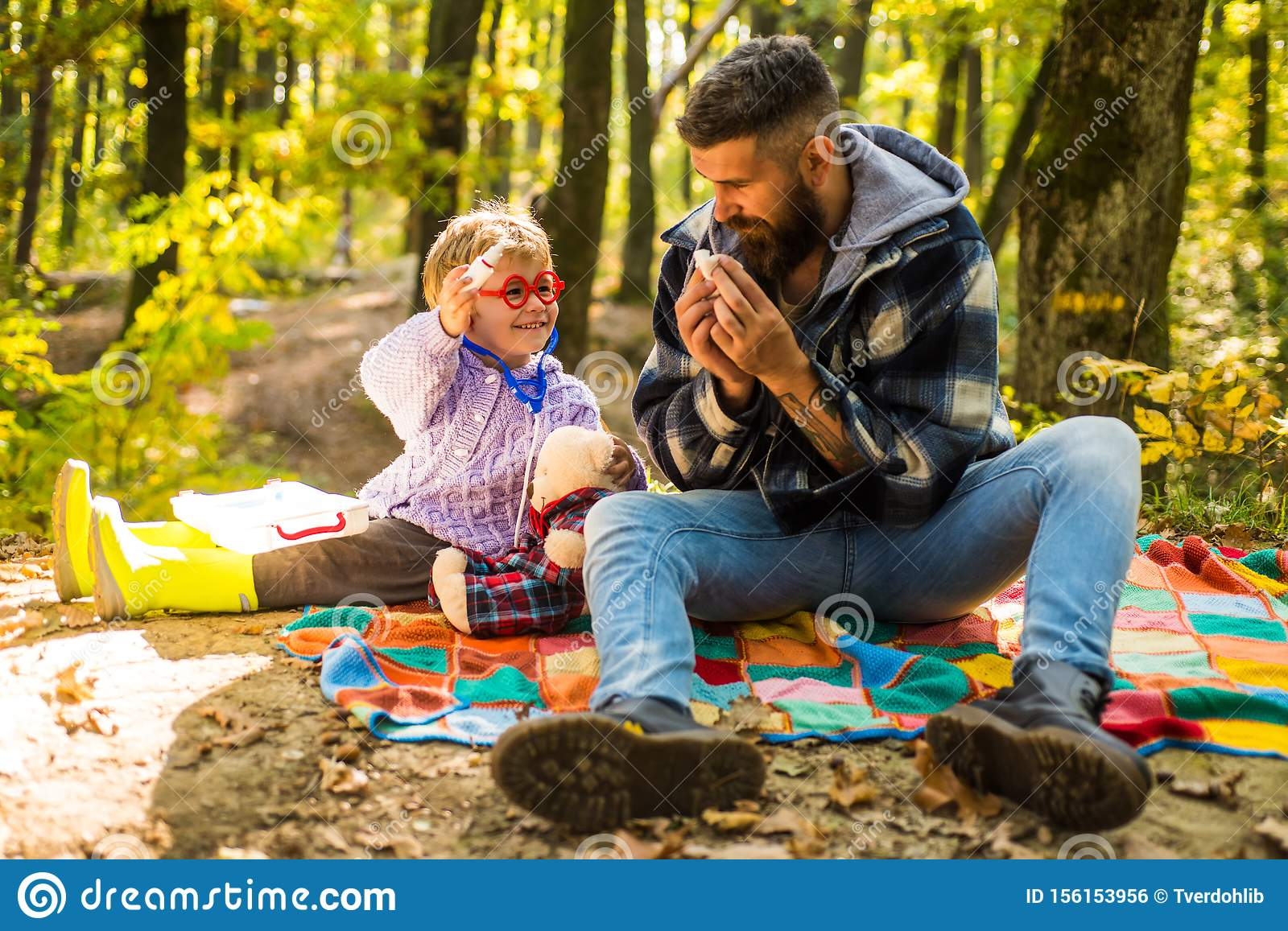 Atumn fun at the park. Sick people has runny nose. Both dad and child are laughing. Little boy with his father in autumn