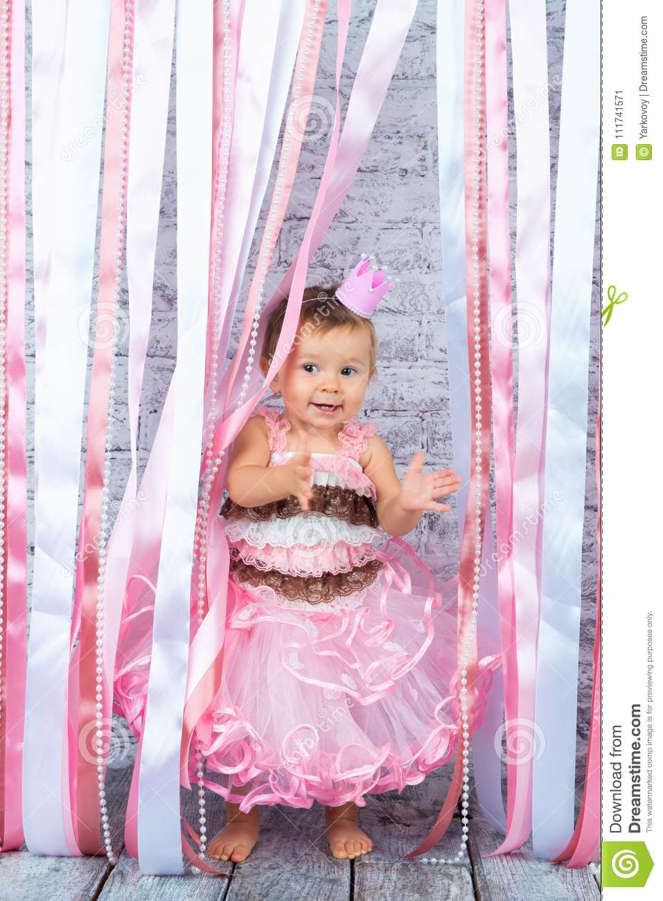 1462a660cff3 A Sweet Little Girl In A Crown And A Beautiful Pink Dress Is Raising ...
