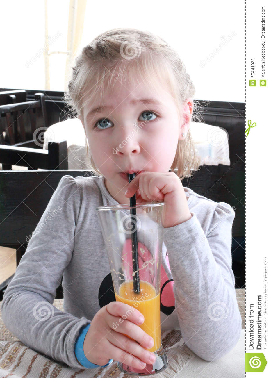 sweet little girl is drinking orange juice through a straw