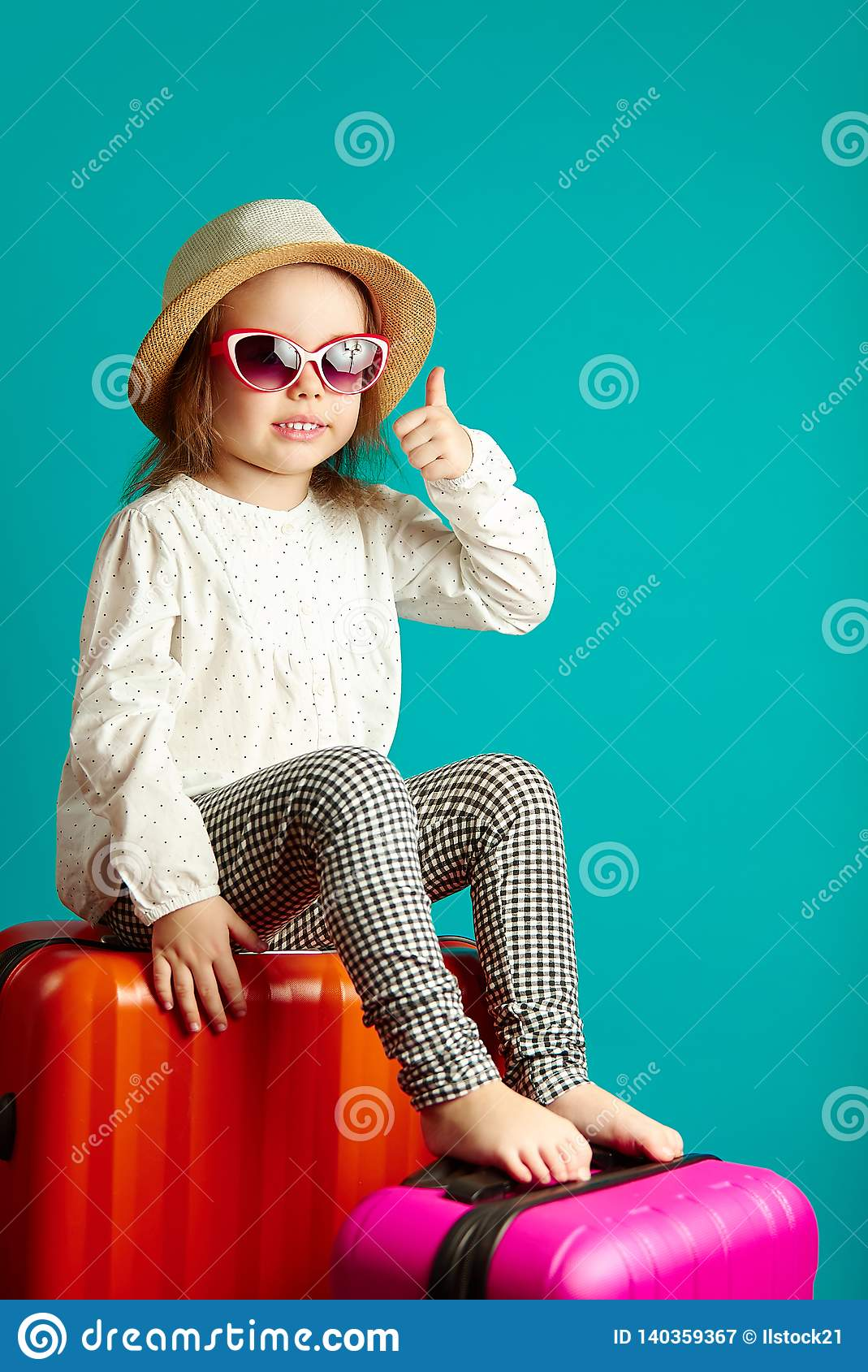 Sweet little girl sits on suitcases, waiting for trip, portrait of happy child on isolated blue.