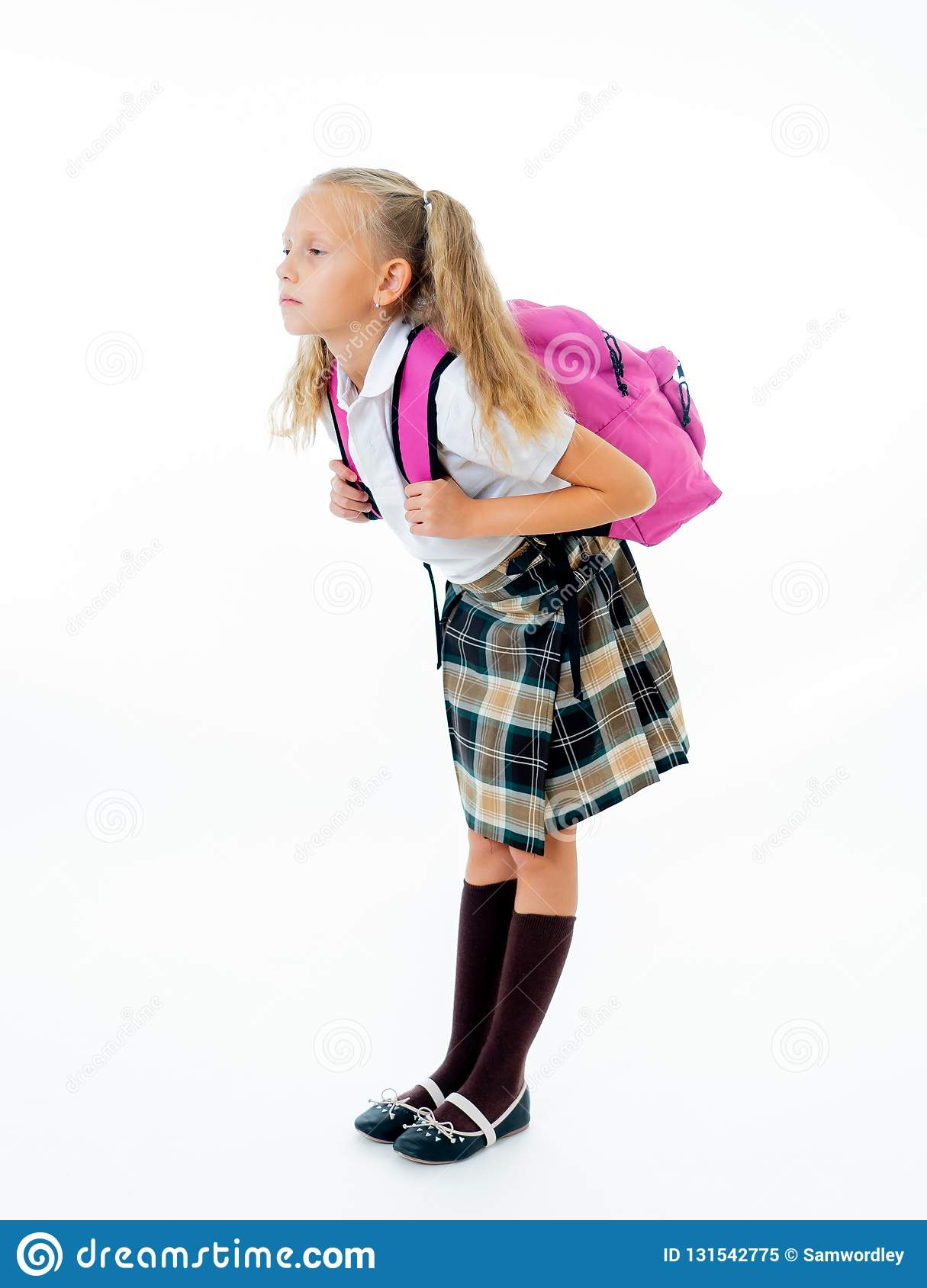 Sweet little girl in uniform carrying heavy big pink backpack or school bag full causing stress and pain on back due to overweight