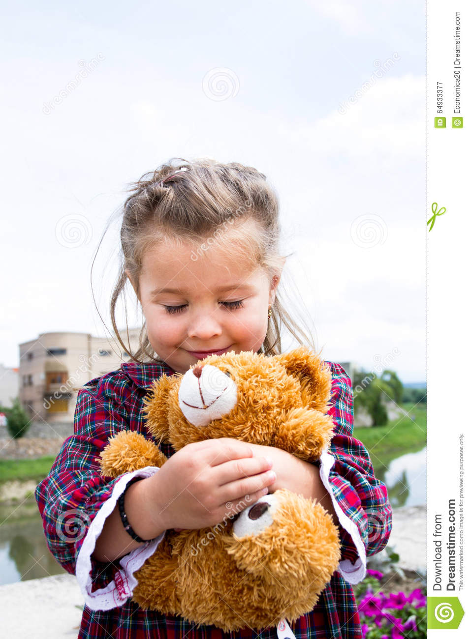 Sweet little holding teddy bear in her arms