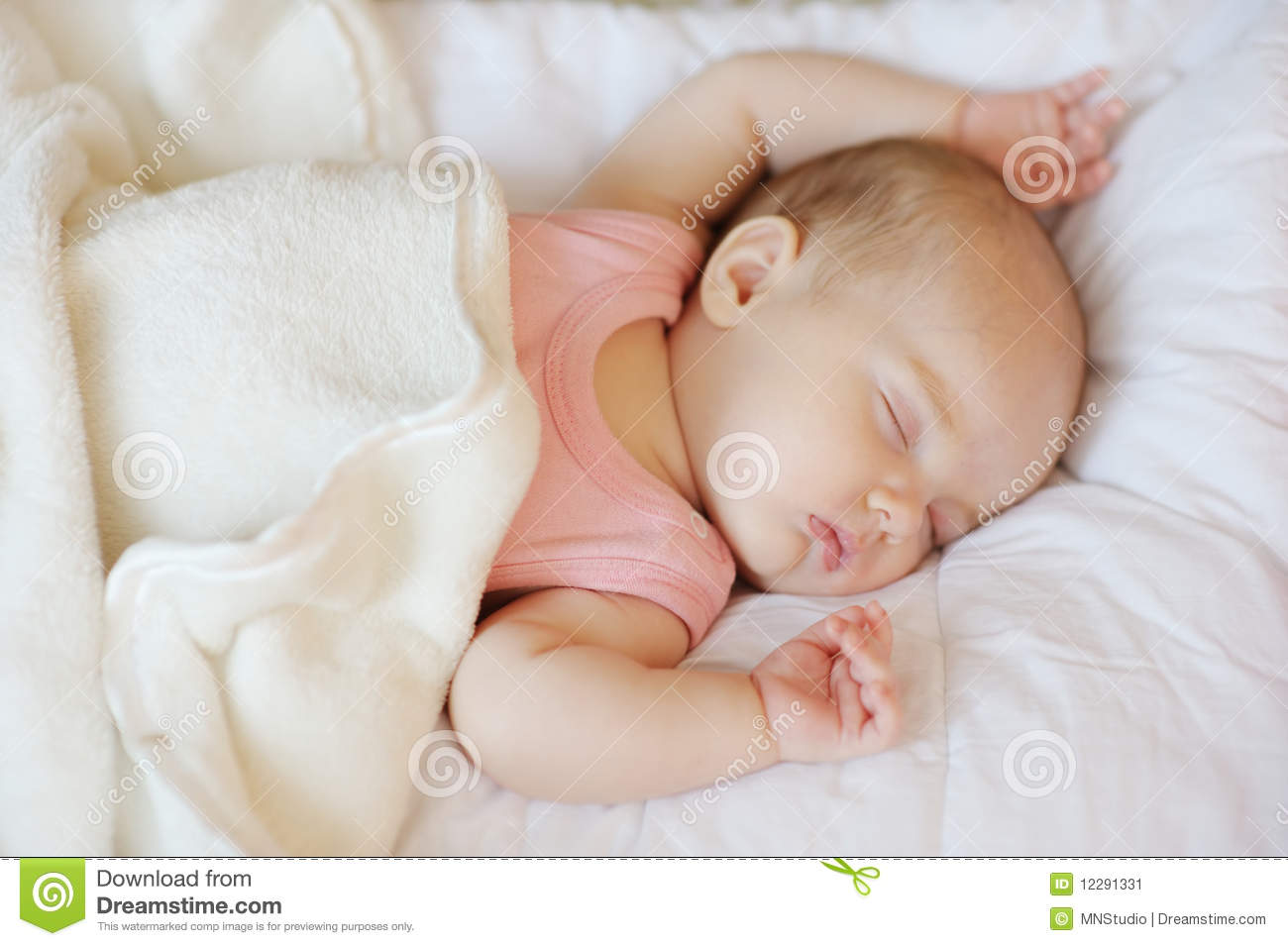 Sweet little newborn baby in a bed