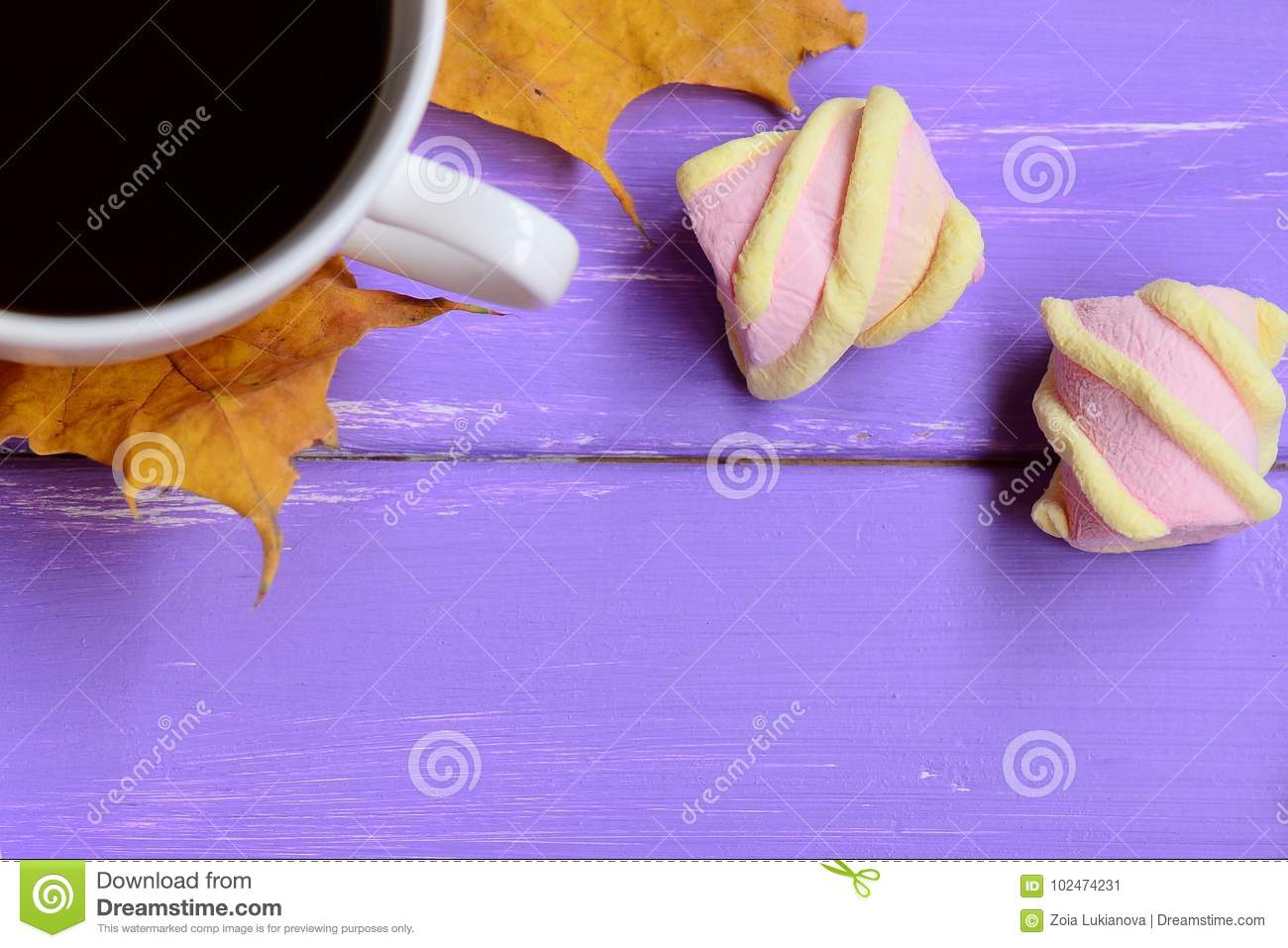 Light pink and yellow marshmallow, yellow autumn leaves, coffee cup on a purple wooden background. Easy autumn coffee break