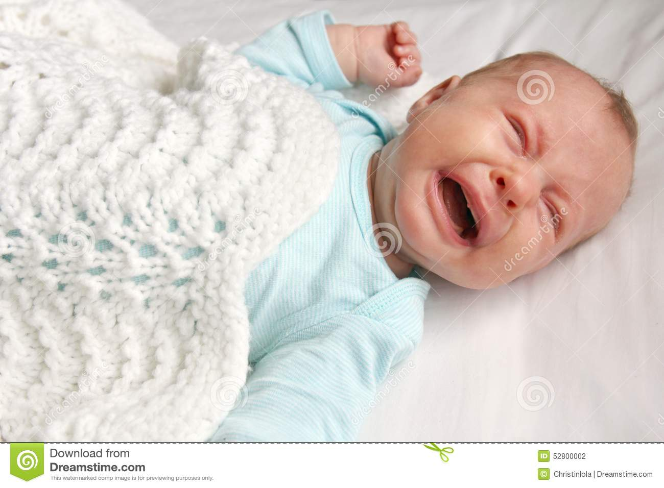 A cute one month old newborn baby is laying on her back in the crib crying