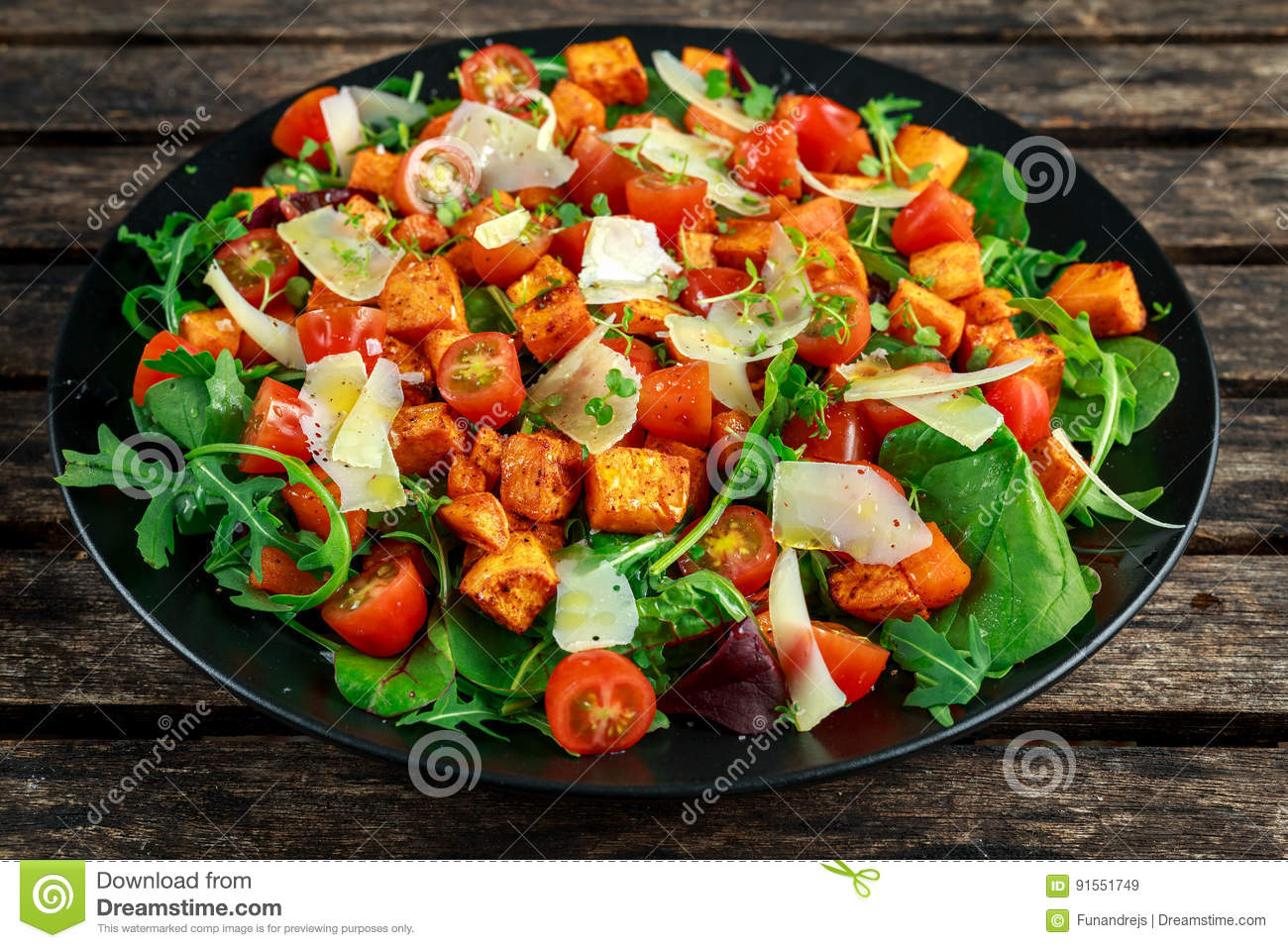 Sweet potato, carrots, cherry tomatoes and wild rocket salad with feta cheese served in black plate