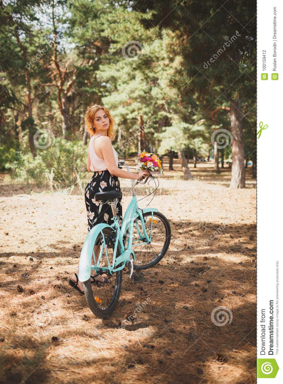 Young smiling girl standing next to a bicycle with a bouquet of flowers in the park The best time to walk with a bicycle