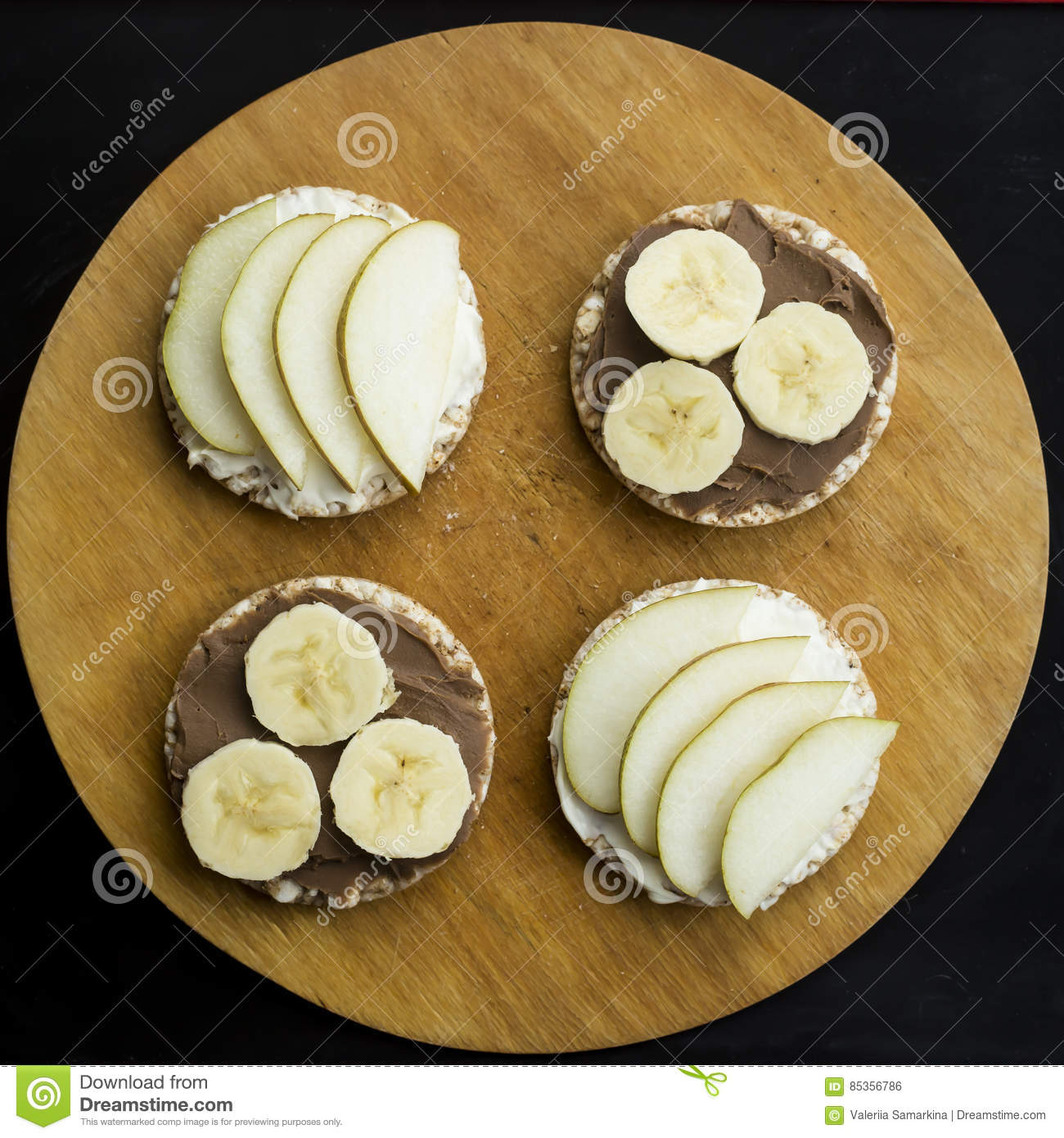 Sweet sandwiches with banana and peanut butter, cheese and pear on circular loaves buckwheat. top view
