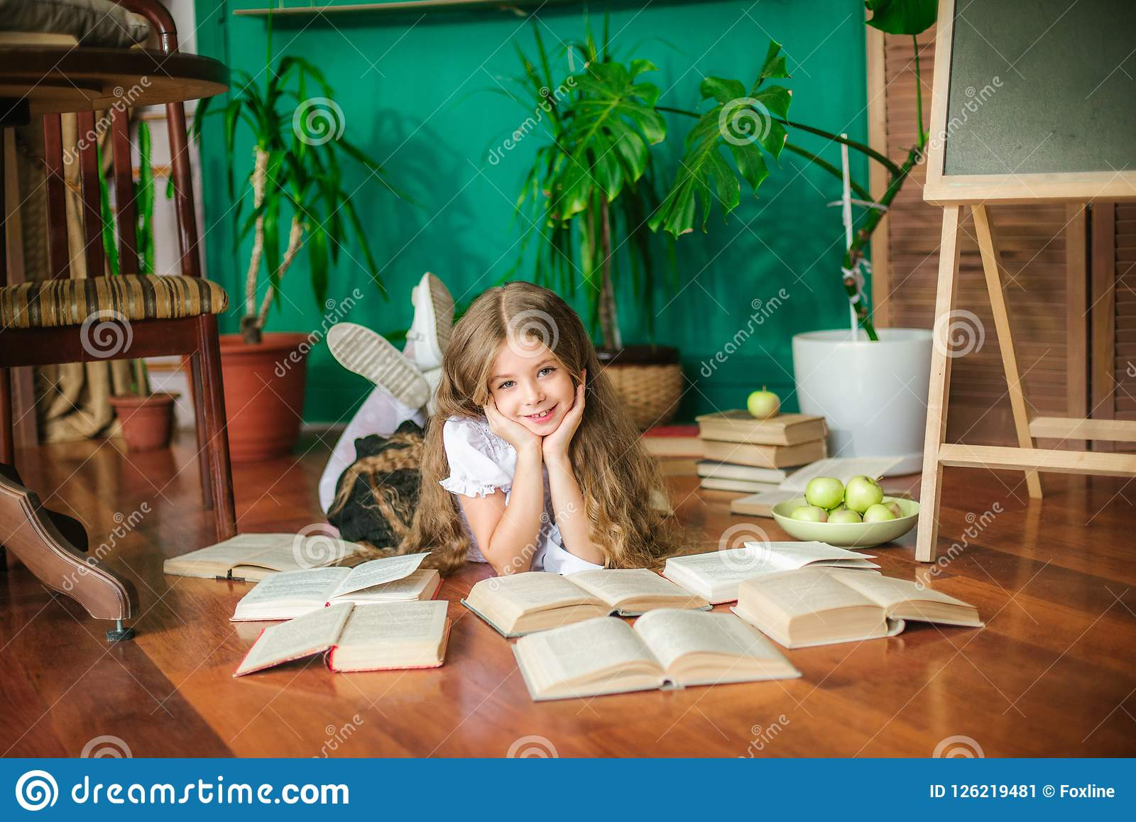 A sweet schoolgirl of junior classes with long blond hair with books, a school board and apples