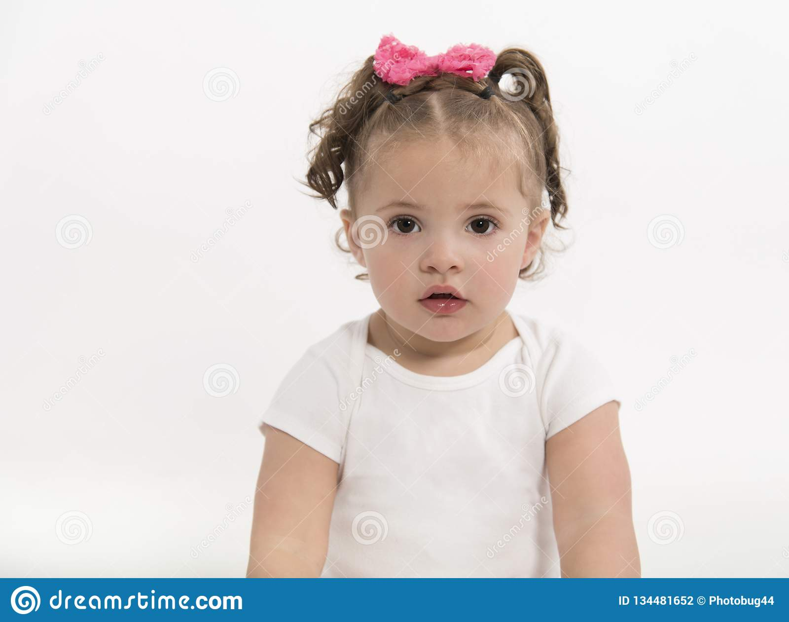 Adorable, Little Girl With Big Brown Eyes And Serious Expression