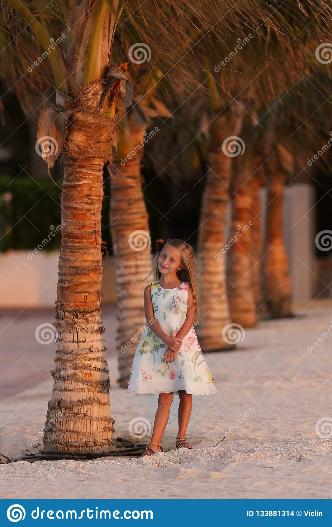 Sweet smiling girl near the palm trees on vacation