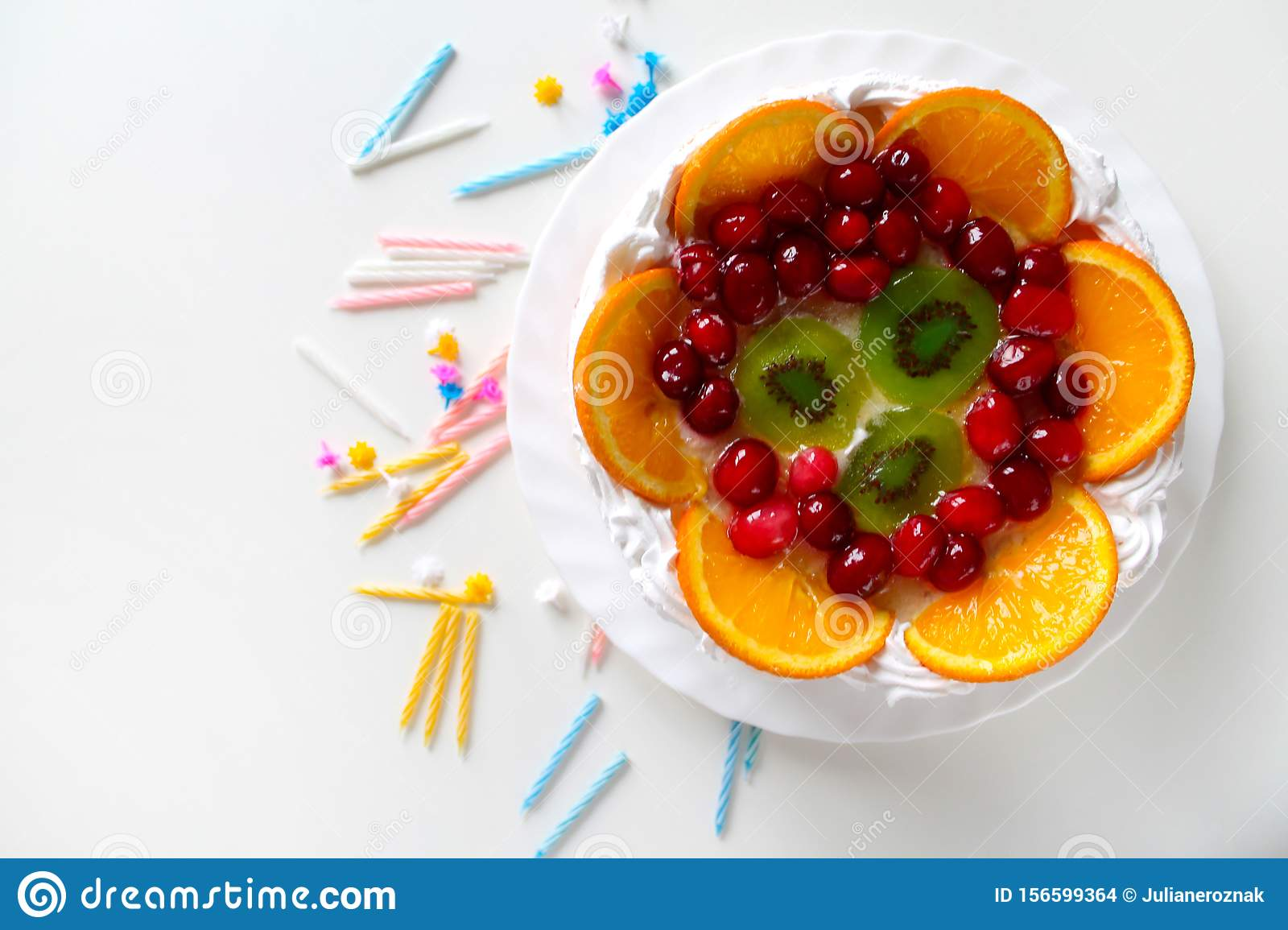 Sweet tasty cake with cream, fresh fruit and jelly. Twisted candles scattered around