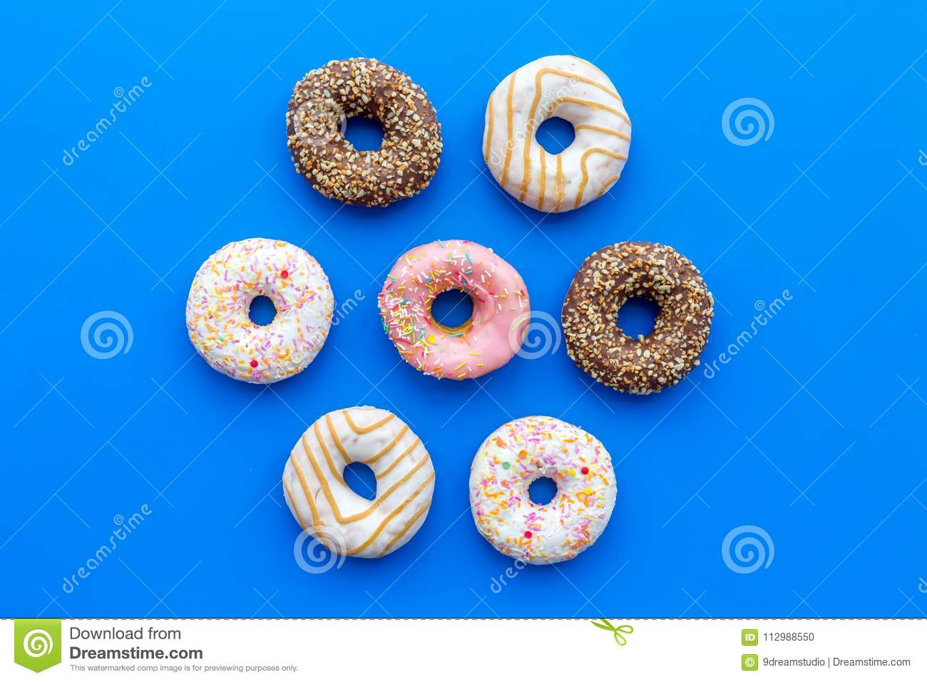 Sweet tasty snack. Glazed donut on blue background top view copy space