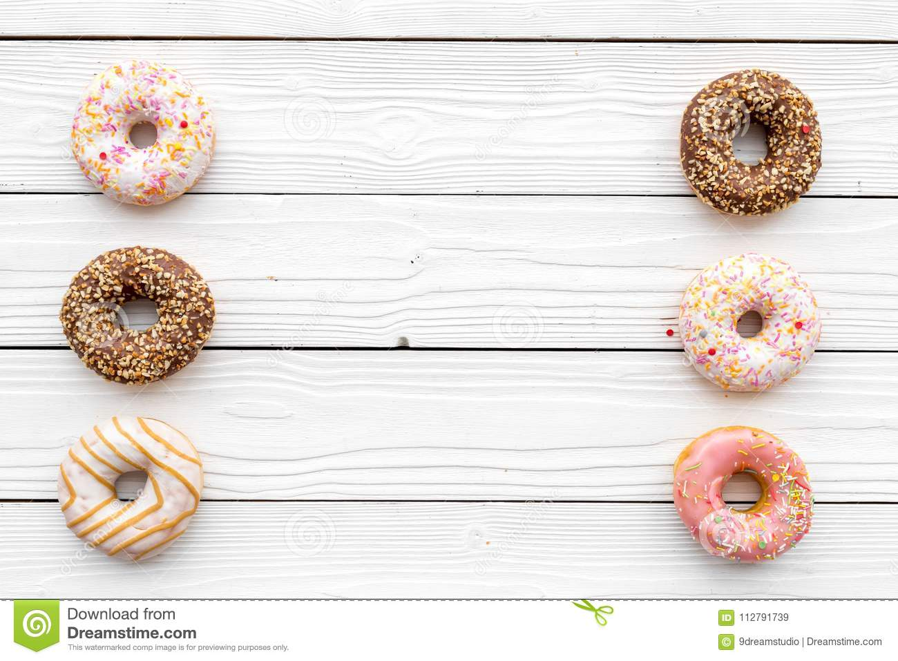Sweet tasty snack. Glazed donut on white wooden background top view copy space