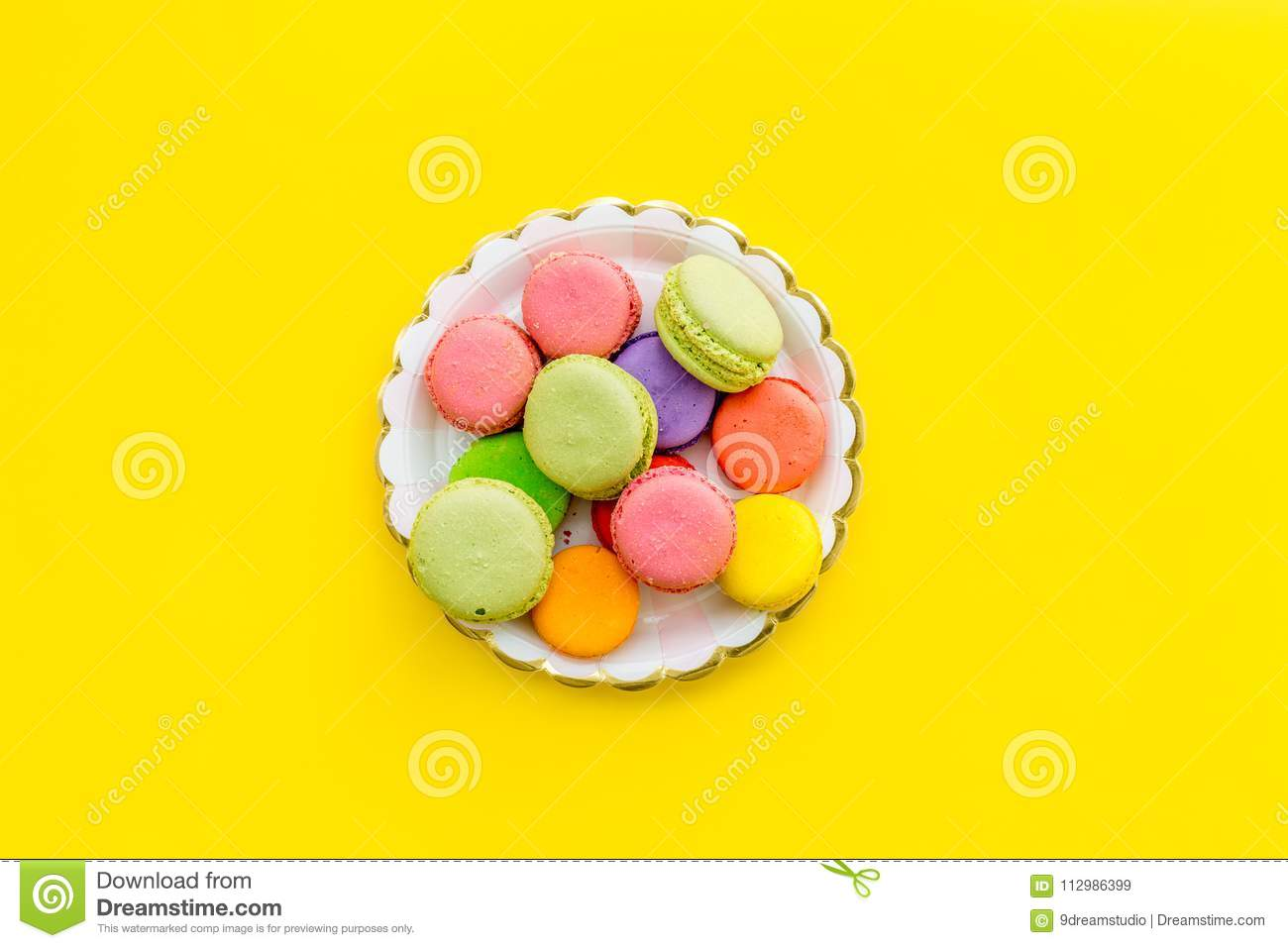 Sweets for party background. Macarons on yellow top view copy space