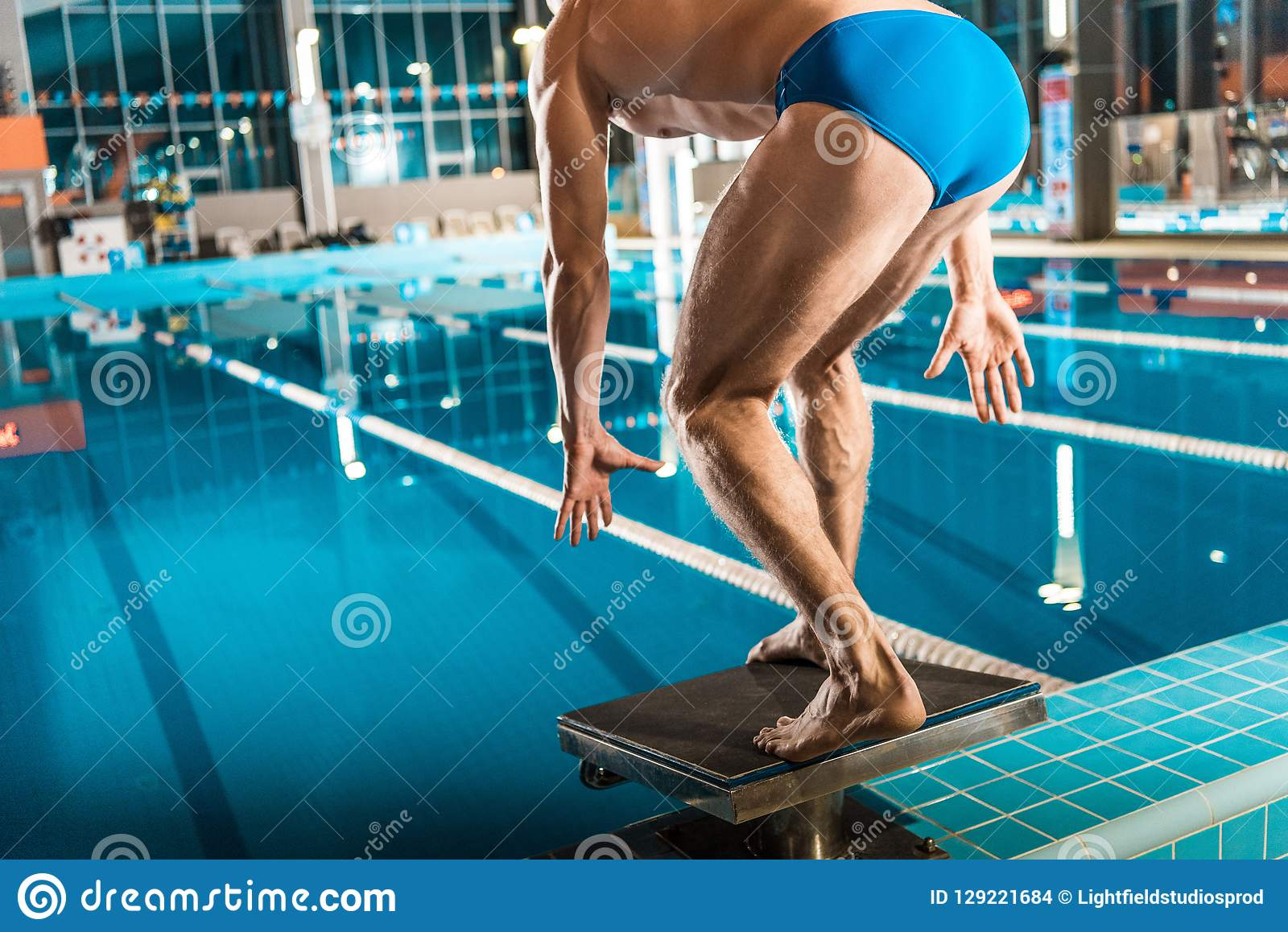 Swimmer Standing On Diving Board Ready To Jump Into Competition ...