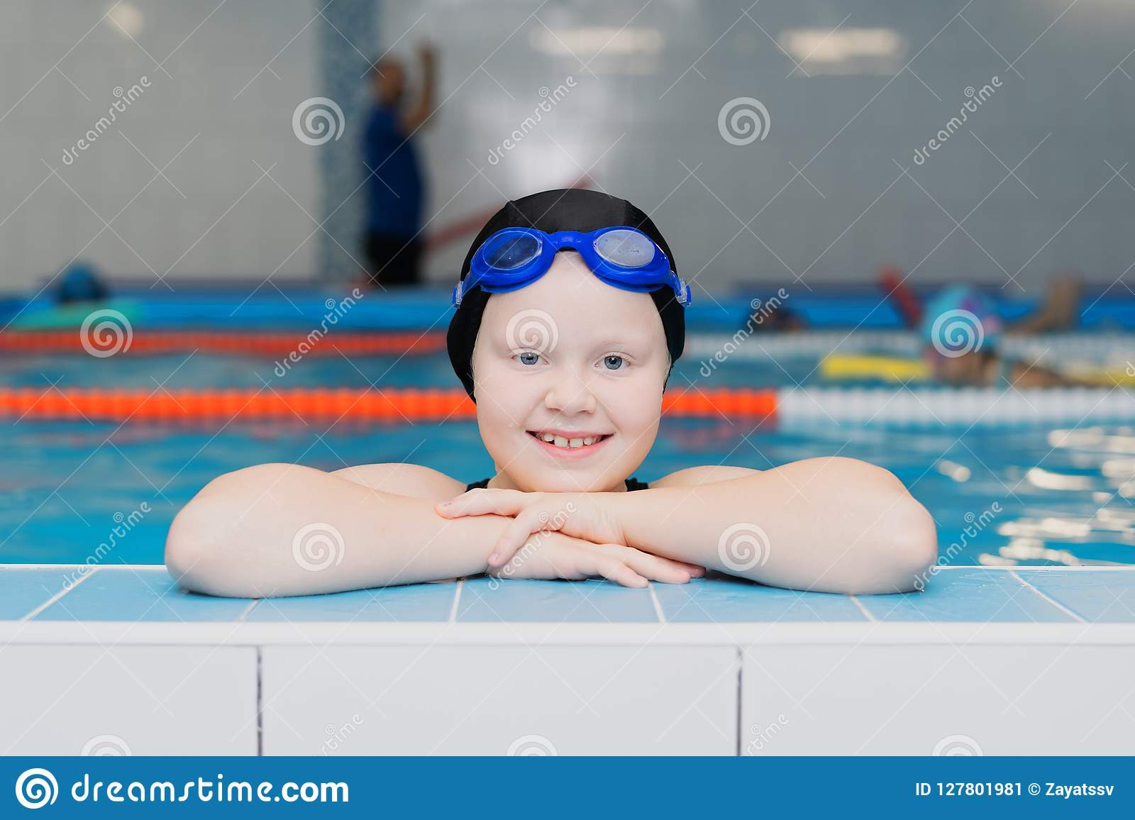 Swimming lessons for children in the pool - portrait of a beautiful white-skinned girl in a bathing suit and swim cap