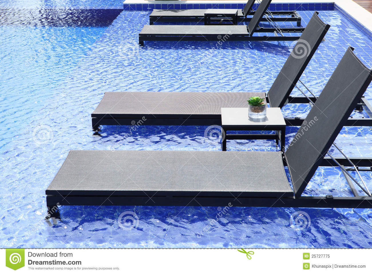 Swimming pool and chairs bed with blue water