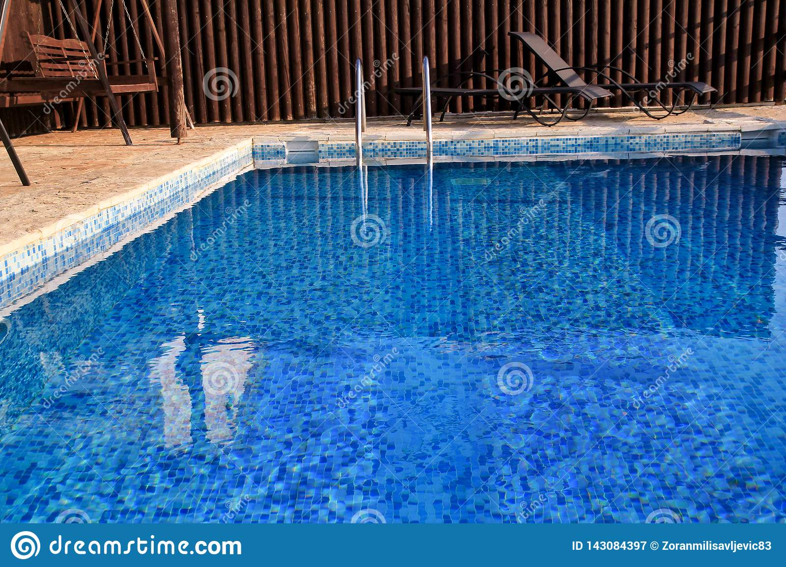 Swimming pool design modern architecture of luxury holiday villa. Relax near exotic swimming pool with handrail, deck chairs, sun