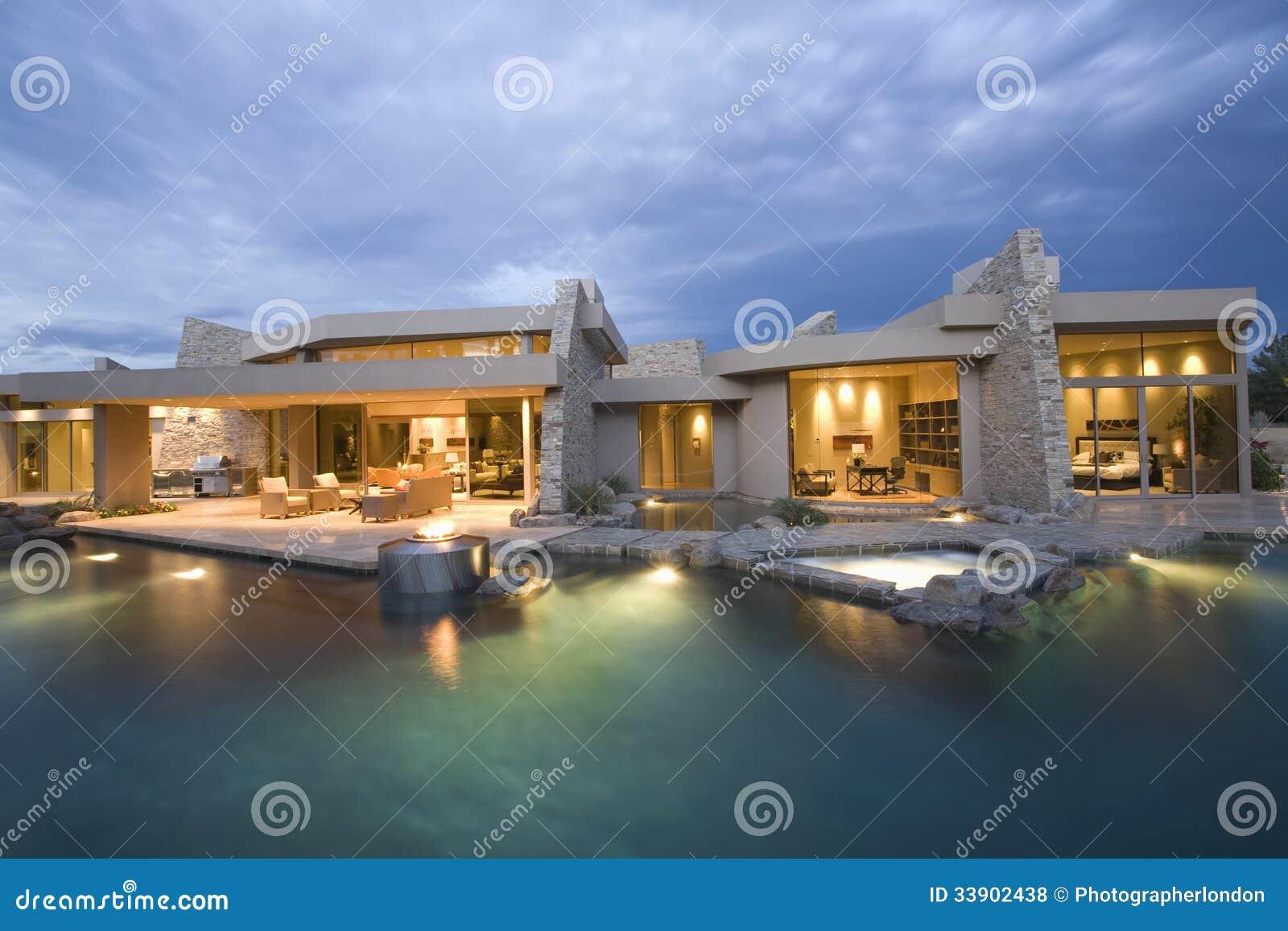 Huis Modern Huis : Swimming pool and illuminated modern house stock photo image of