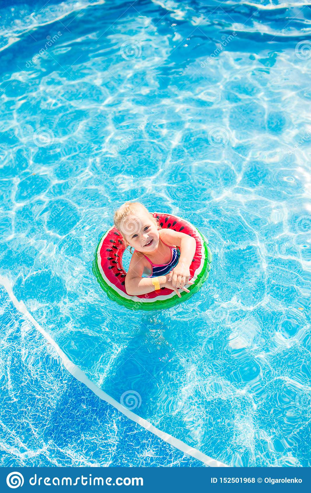 Swimming, summer vacation - lovely smiling girl playing in blue water with lifebuoy-watermelon
