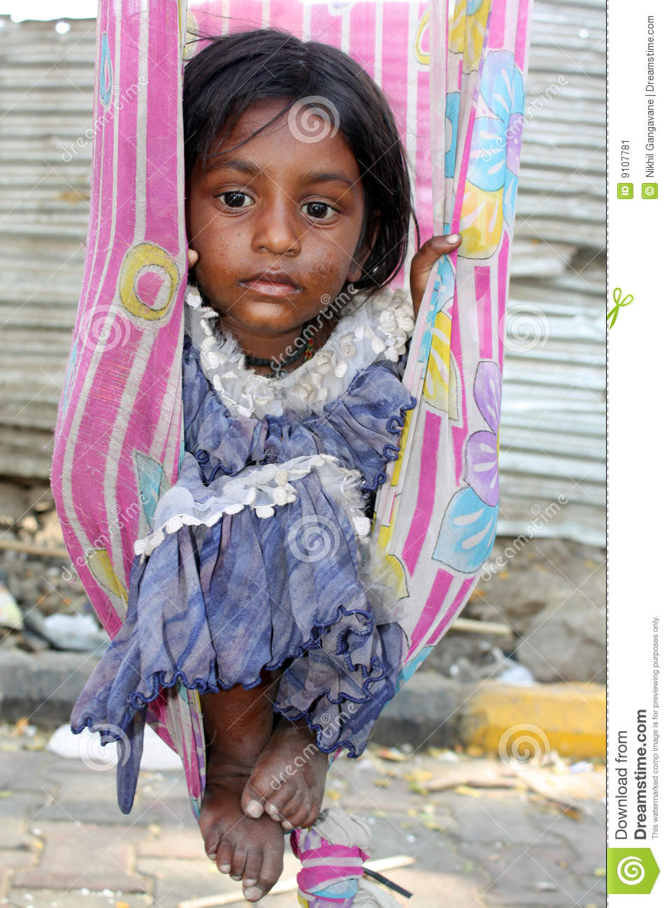 The very poor sick Indian girl sitting in a swing made of an old sari  (traditional women clothes), lost in her thoughts.