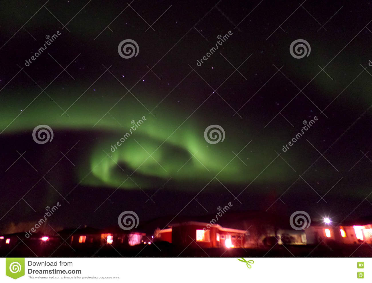 Swirling Aurora Borealis over a Small Town in North Iceland