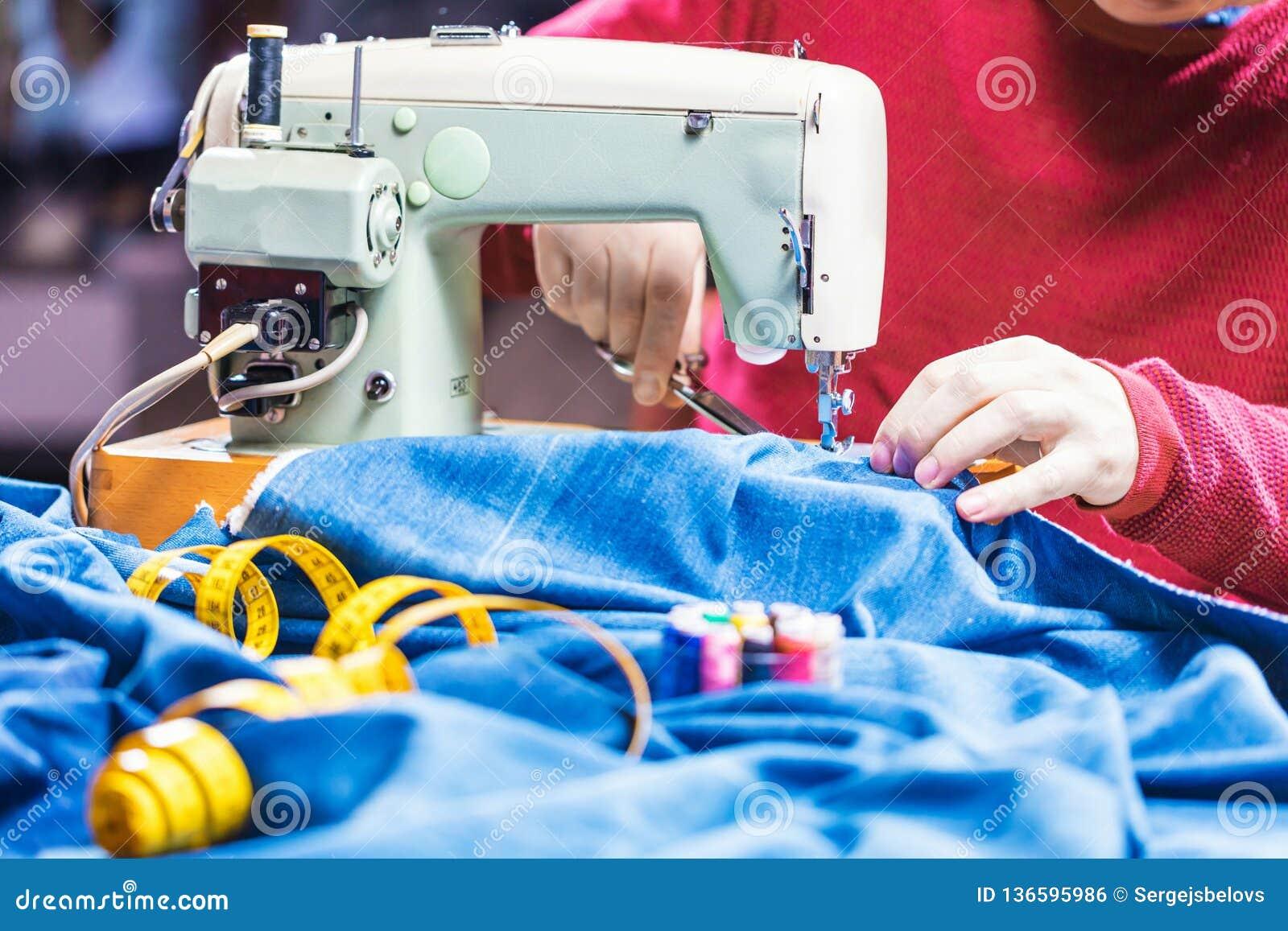 Sy grov bomullstvilljeans med symaskinen Reparationsjeans vid symaskinen Förändringsjeans som fållar ett par jeans som är handgjo