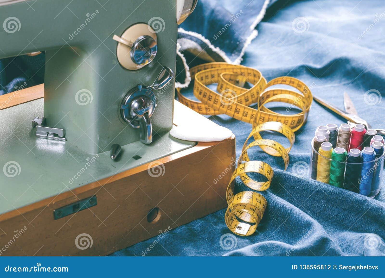 Sy indigoblå grov bomullstvilljeans med symaskinen, industriellt begrepp för plagg