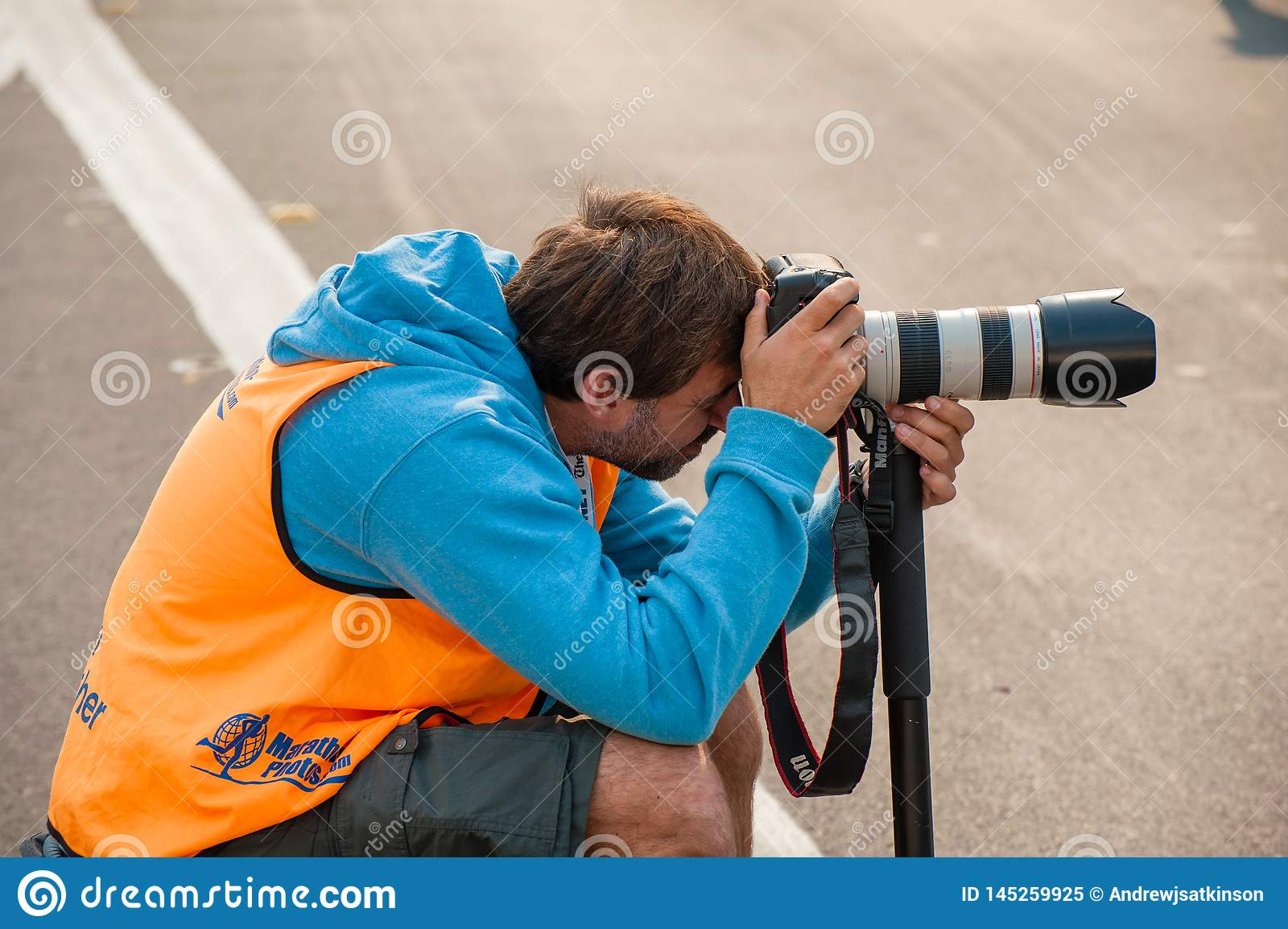 Official photographer crouching taking photos with a DSLR and zoom lens
