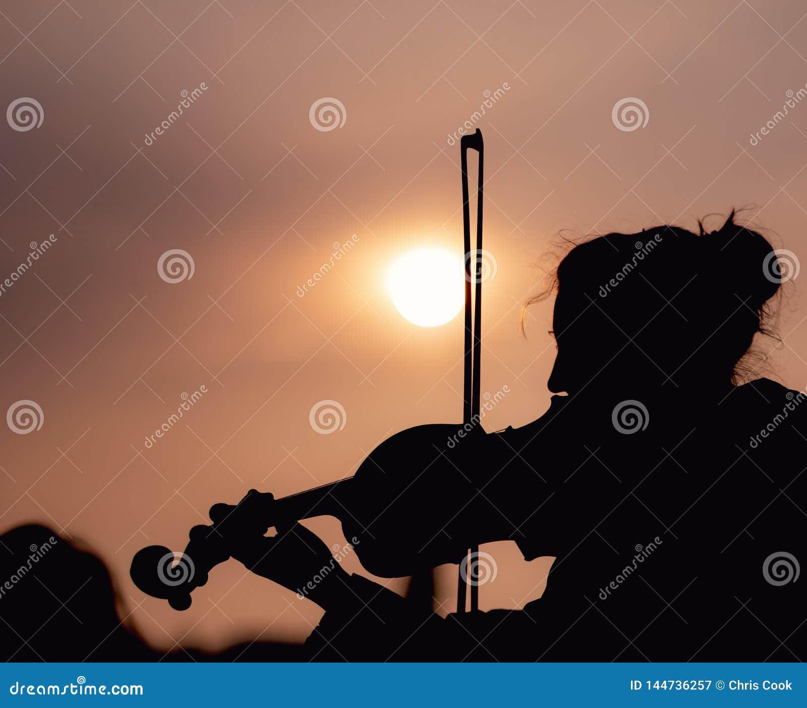 Sylwetka bawić się skrzypce podczas zmierzchu przeciw słońcu kobieta - Nabierający Praga