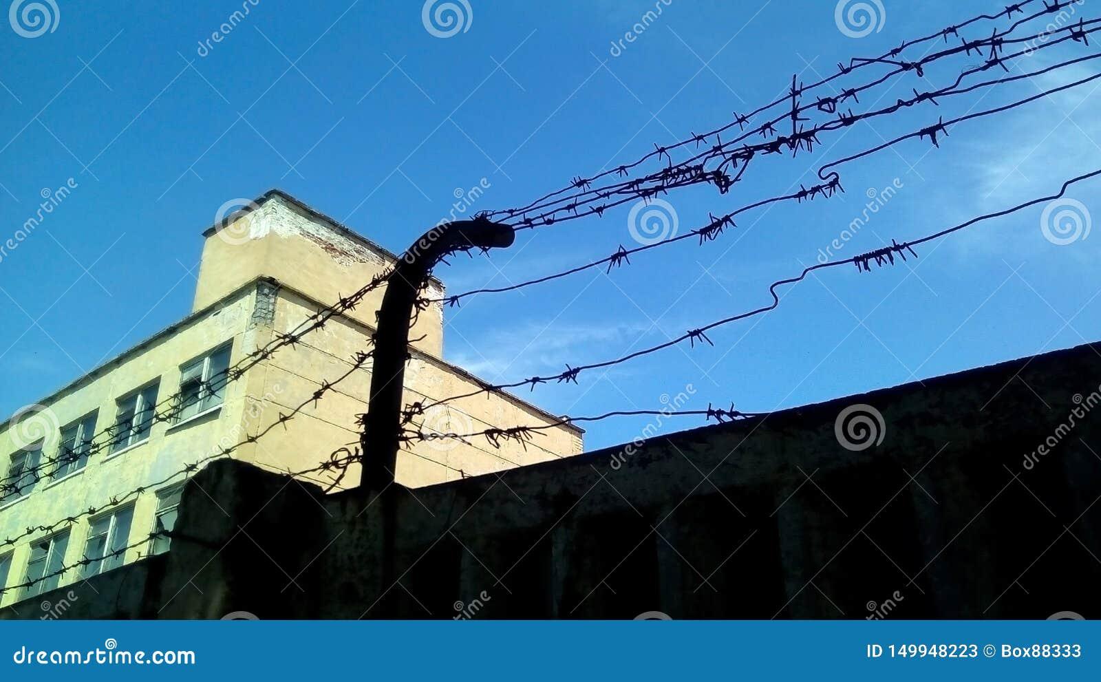 Sylwetka betonowy ogrodzenie z drutem kolczastym