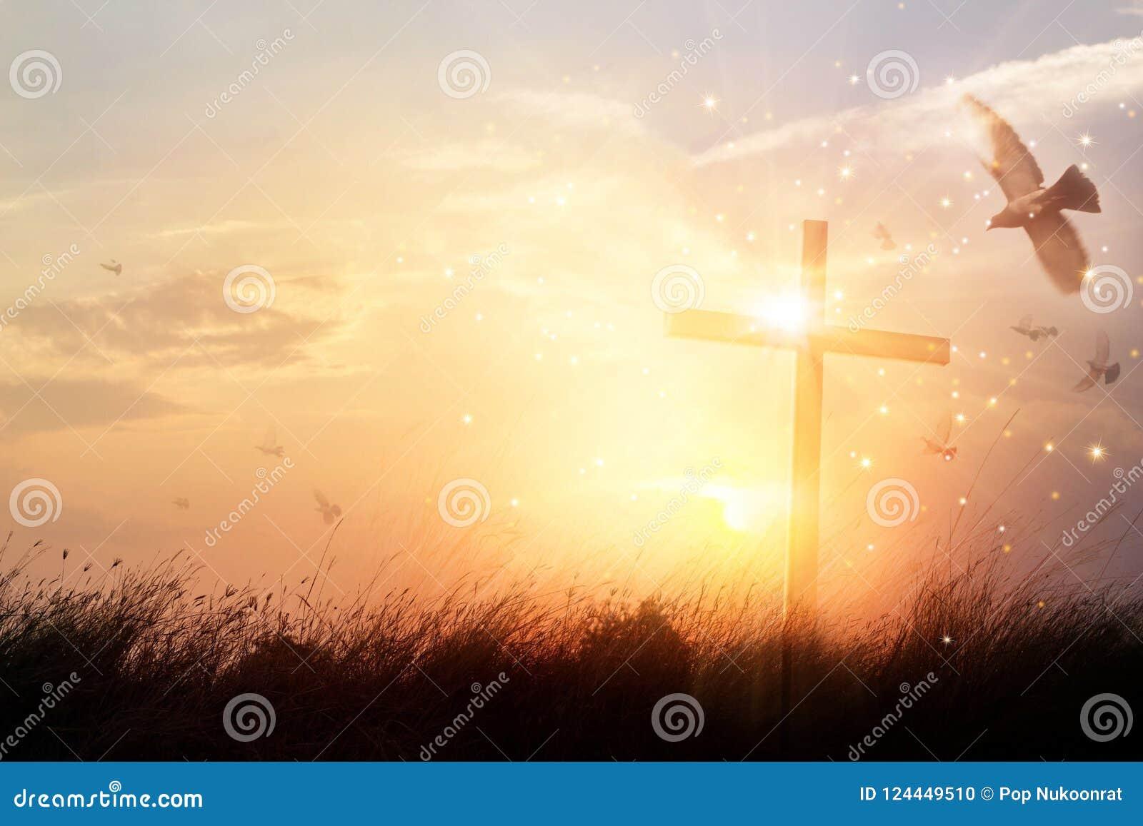 Sylwetka chrześcijanina krzyż na trawie w wschodu słońca tle