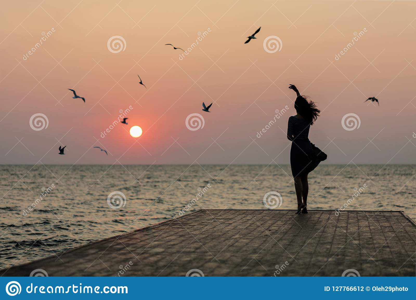 Sylwetka dziewczyna na zmierzchu tła wschodzie słońca na morzu