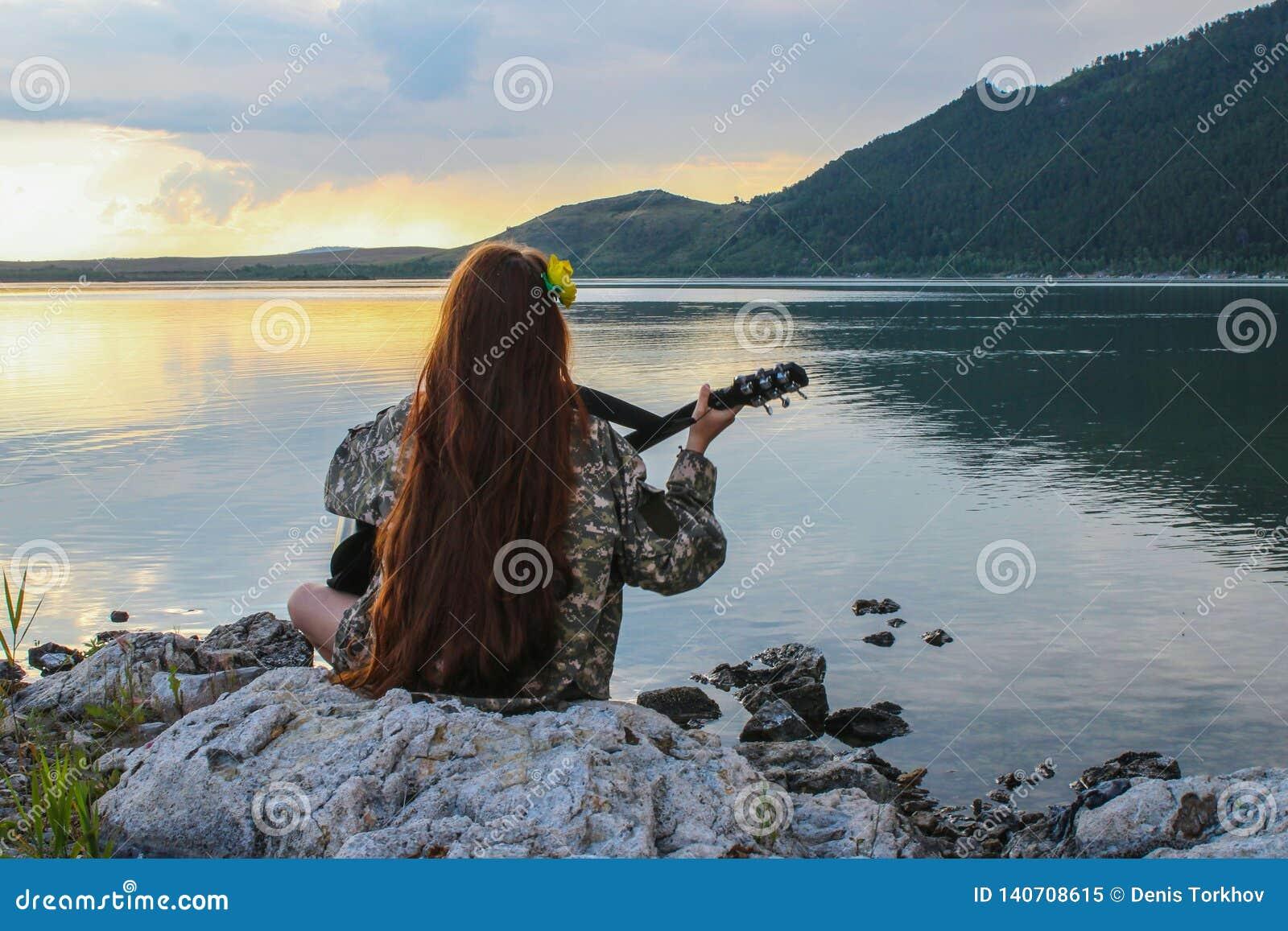 Sylwetka dziewczyna przy zmierzchem bawić się gitarę rzeką