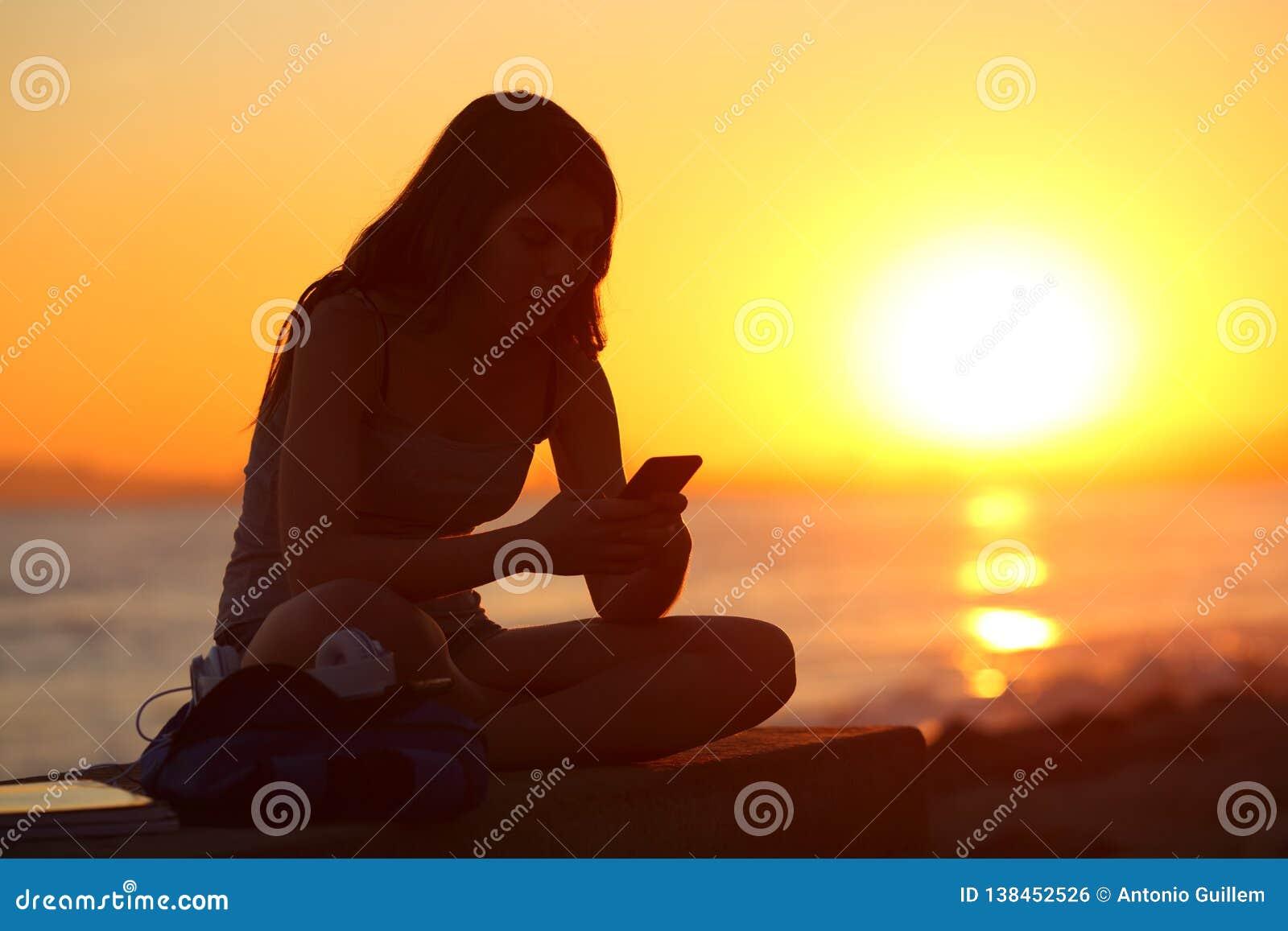 Sylwetka dziewczyna używa mądrze telefon przy zmierzchem