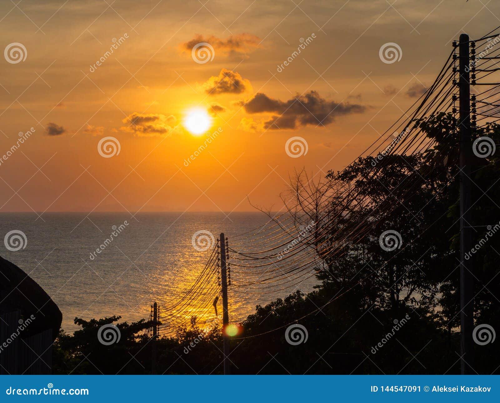 Sylwetka elektryczni druty przeciw słońca położeniu w morzu