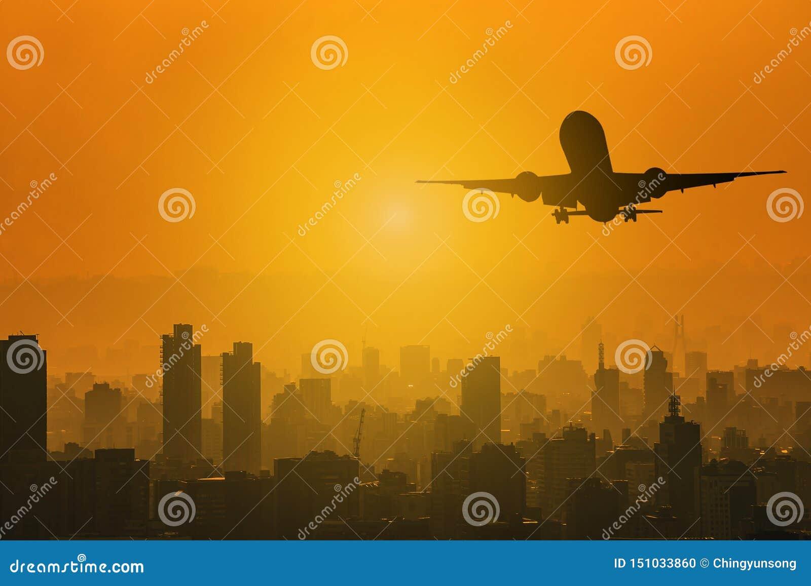 Sylwetka lata nad miastem z podczas skylight zmierzchu z kopii przestrzenią dla teksta handlowy samolot