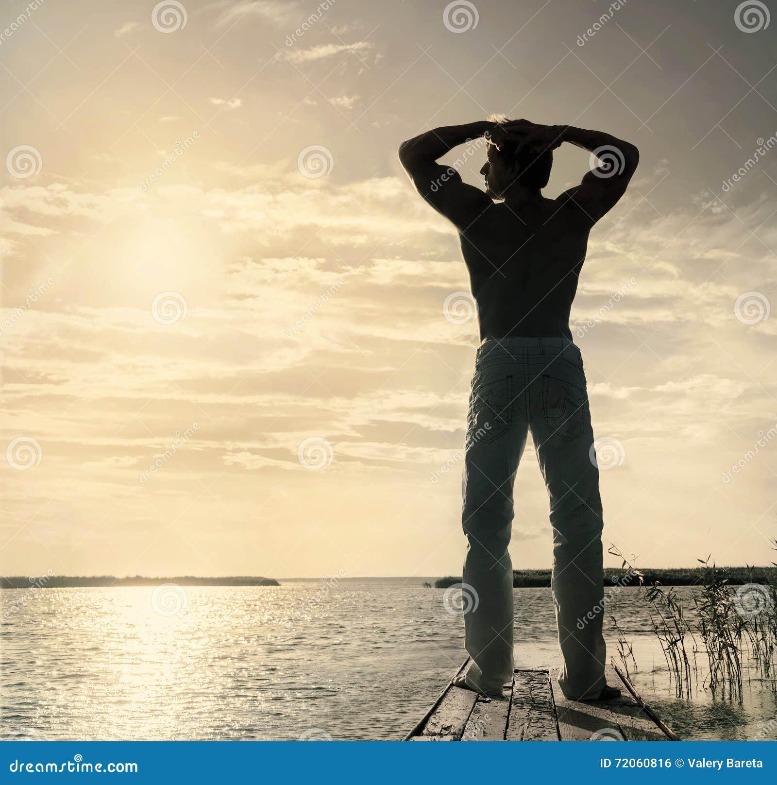 Sylwetka mężczyzna pozycja na małym drewnianym jetty przy latem pogodnym