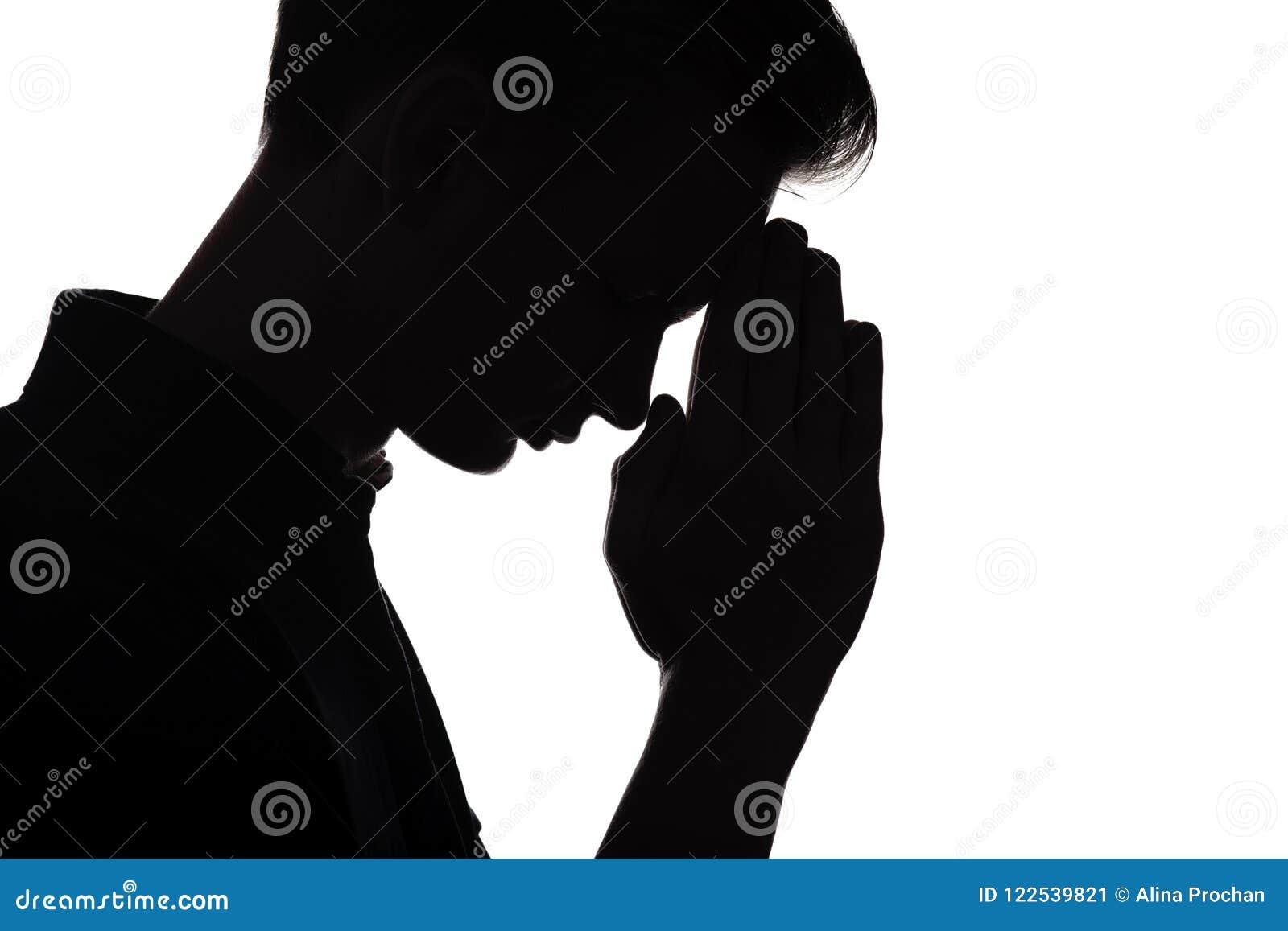 Sylwetka modlenie młody człowiek na białym odosobnionym tle