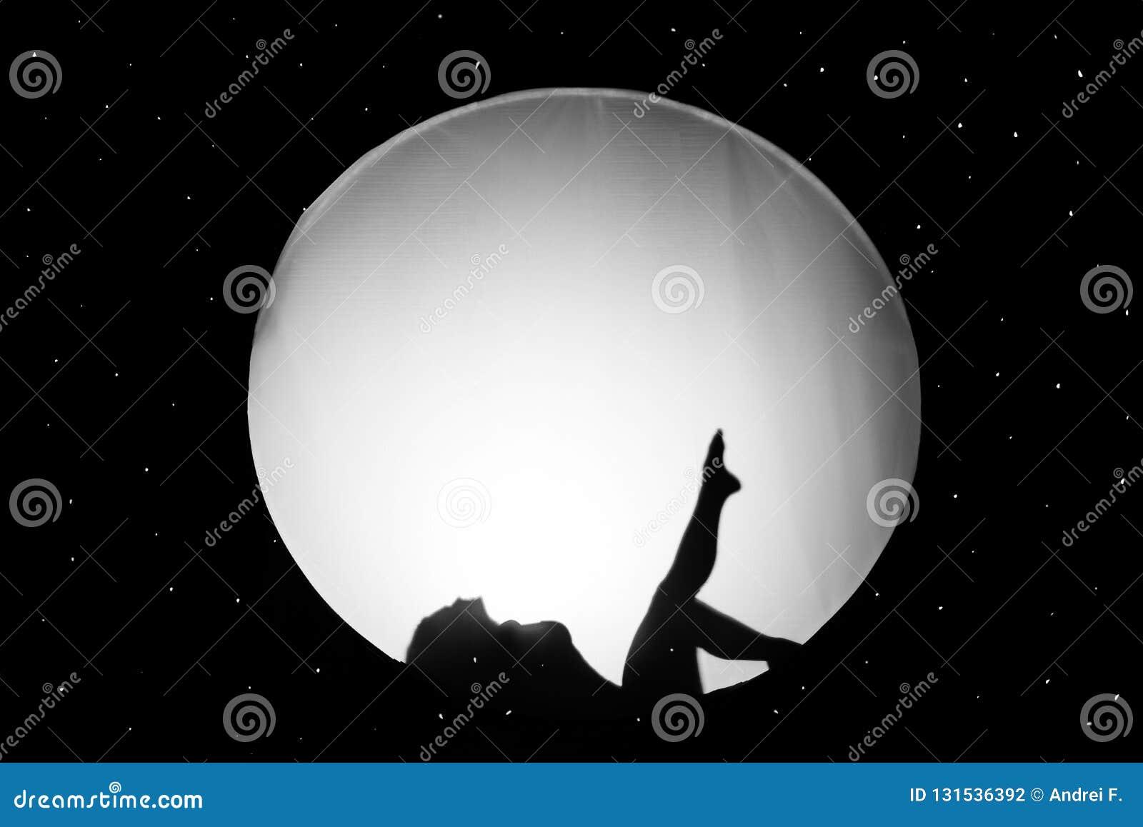 Sylwetka naga dziewczyna przeciw białemu tłu w postaci okręgu w czerni przestrzeni,