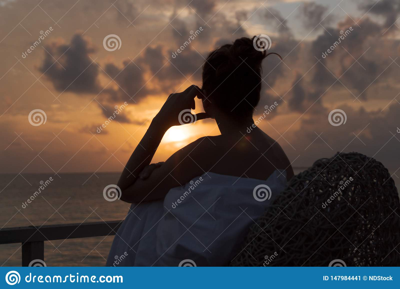 Sylwetka pi?kna kobieta kontempluje wsch?d s?o?ca od balkonu nad morzem