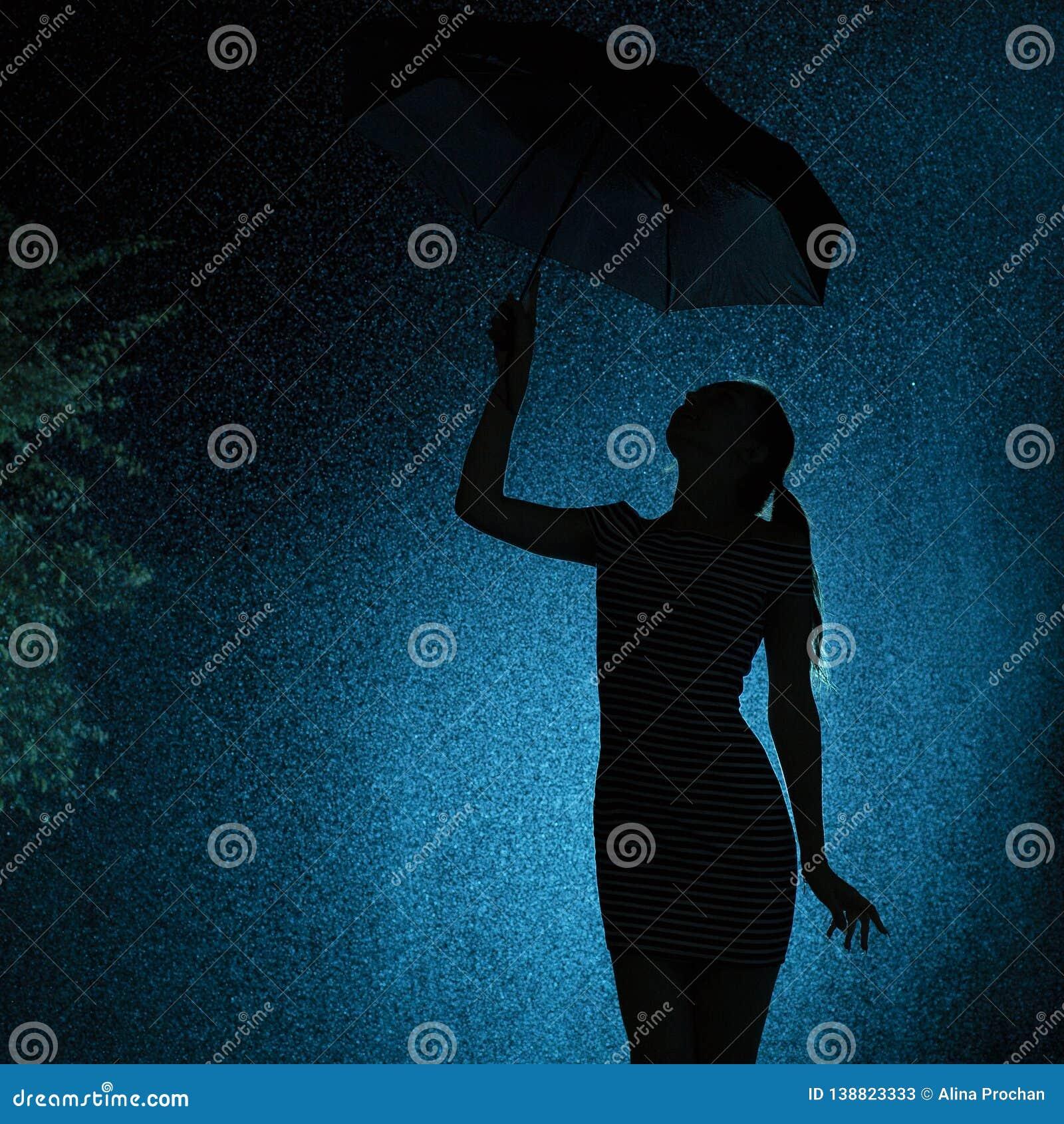 Sylwetka postać młoda dziewczyna z parasolem w deszczu, młoda kobieta z wskazanym włosy jest szczęśliwa krople