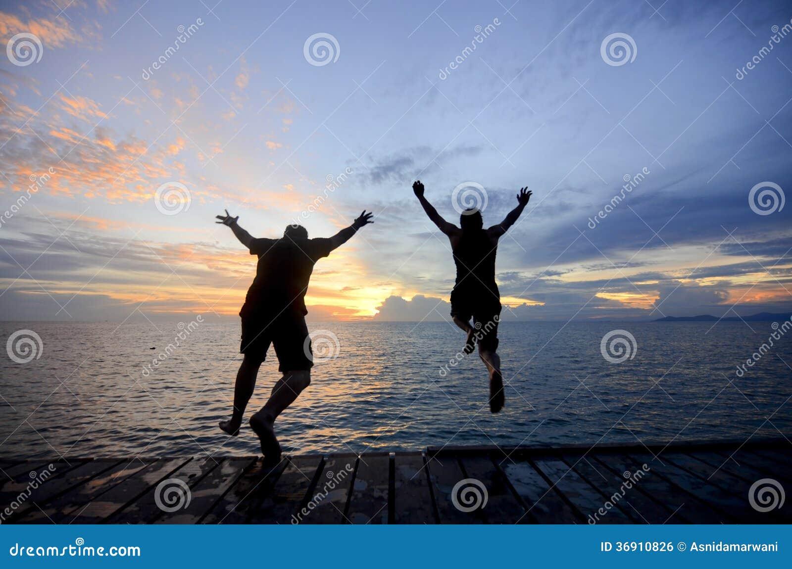 Sylwetka przyjaciela doskakiwanie w morze podczas złotego zmierzchu