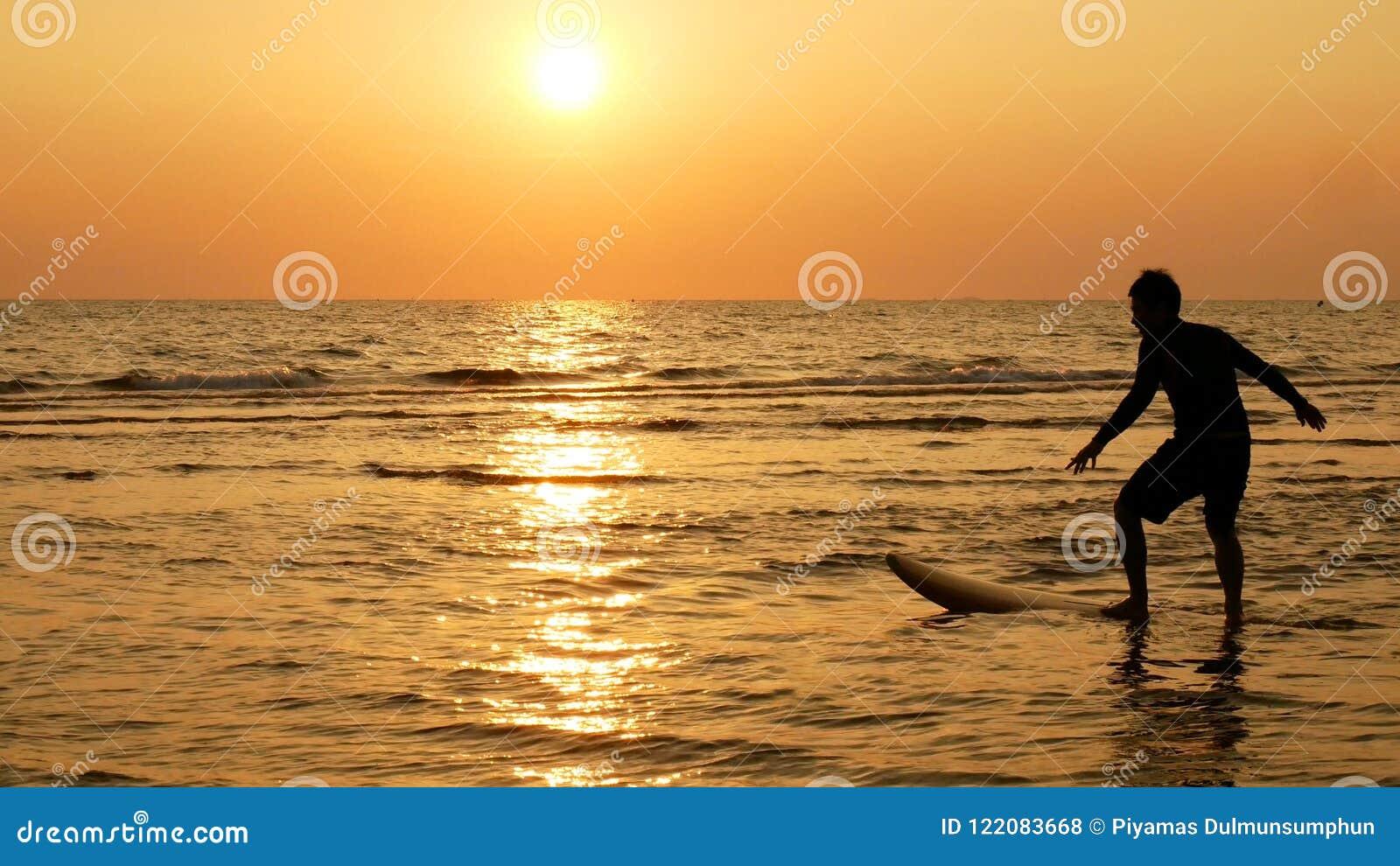 Sylwetka szczęśliwy kipiel mężczyzna surfing z długimi kipieli deskami przy zmierzchem na tropikalnej plaży