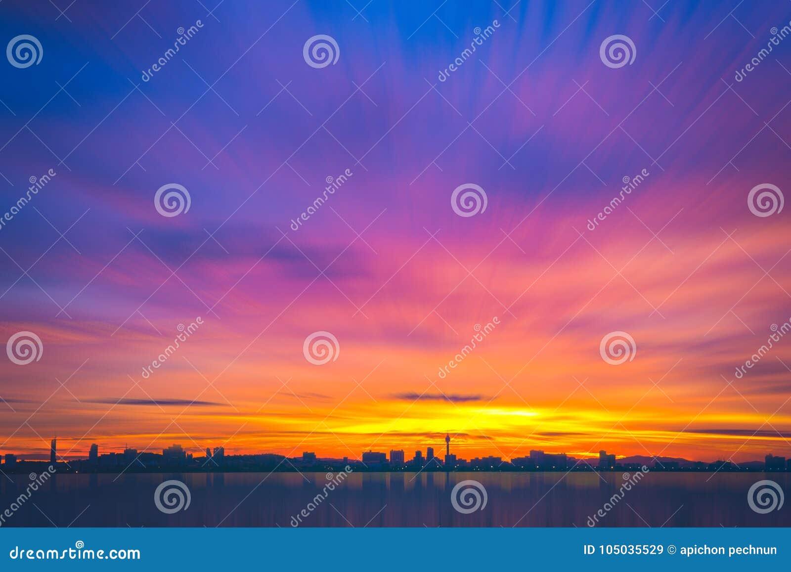 Sylwetka wysocy budynki z pięknym niebem i morzem przy zmierzchem K