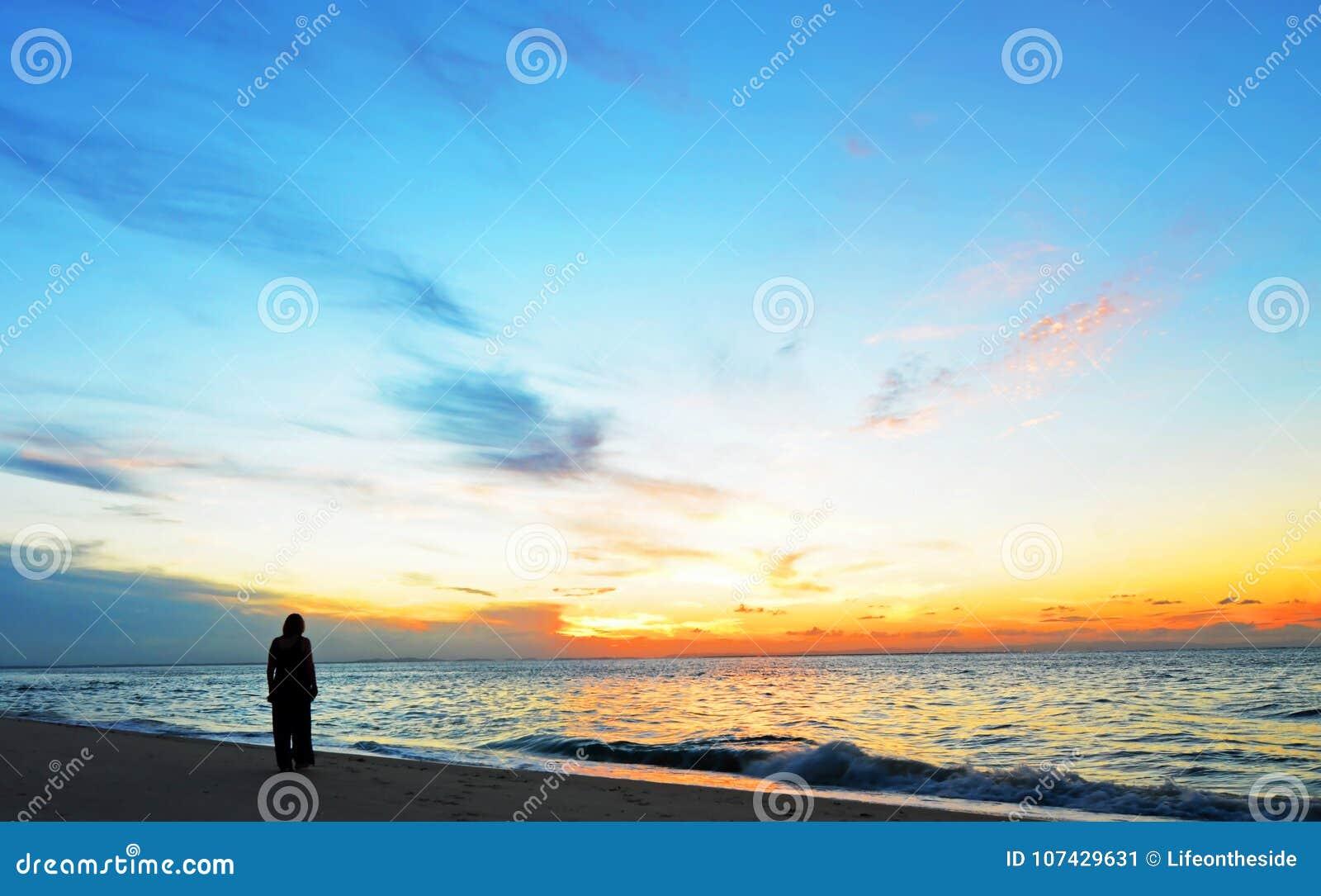 Sylwetki kobieta, zmierzch na oceanu dobrzy stosunki punktu plaży, Północna Stradbroke wyspa, Australia