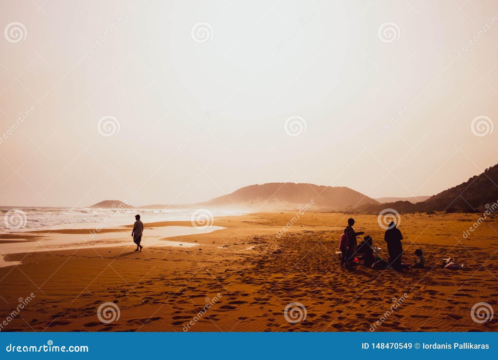 Sylwetki ludzie bawić się w piaskowatej Złotej plaży, Karpasia, Cypr